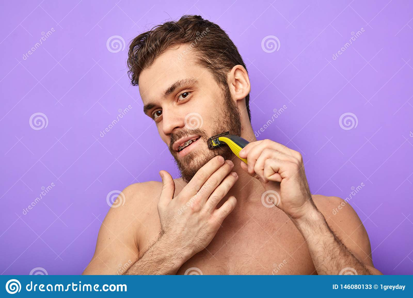 Naked muscular man is standing with razor in hand while shaving.
