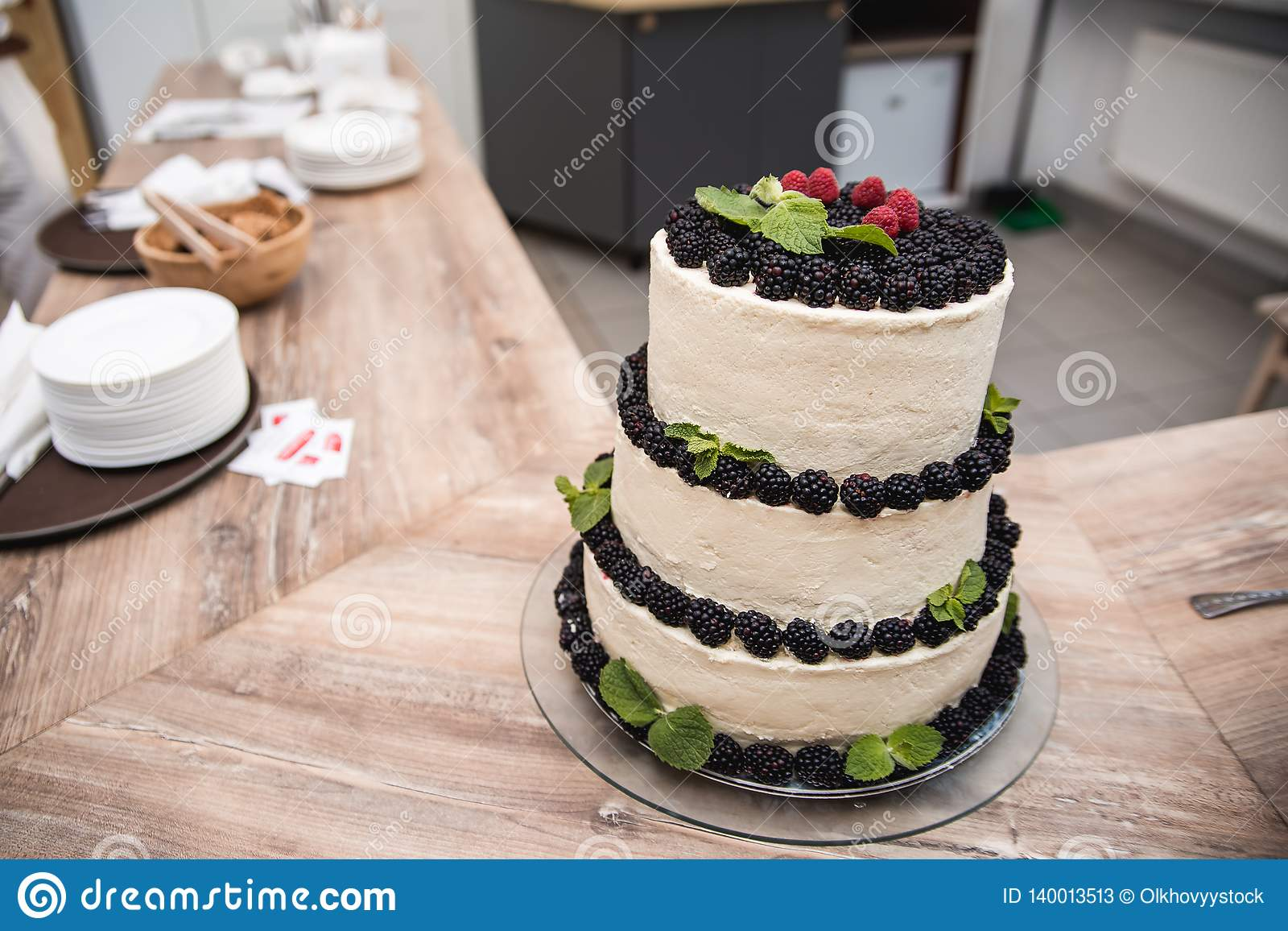 Naked wedding cake decorated with red berries and a dusting of icing sugar