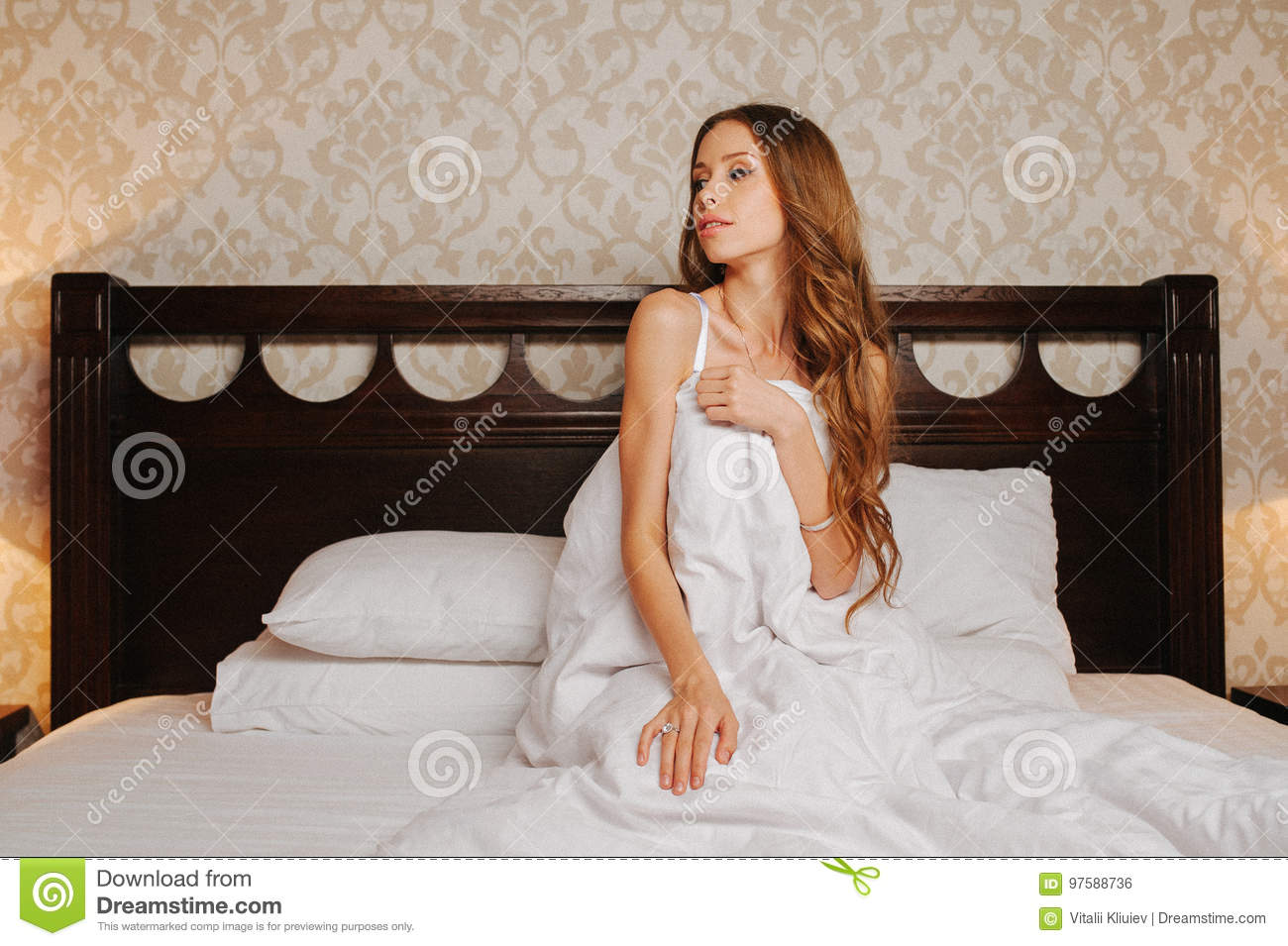 Naked Woman Covered By The Blanket On The Bed Stock Photo
