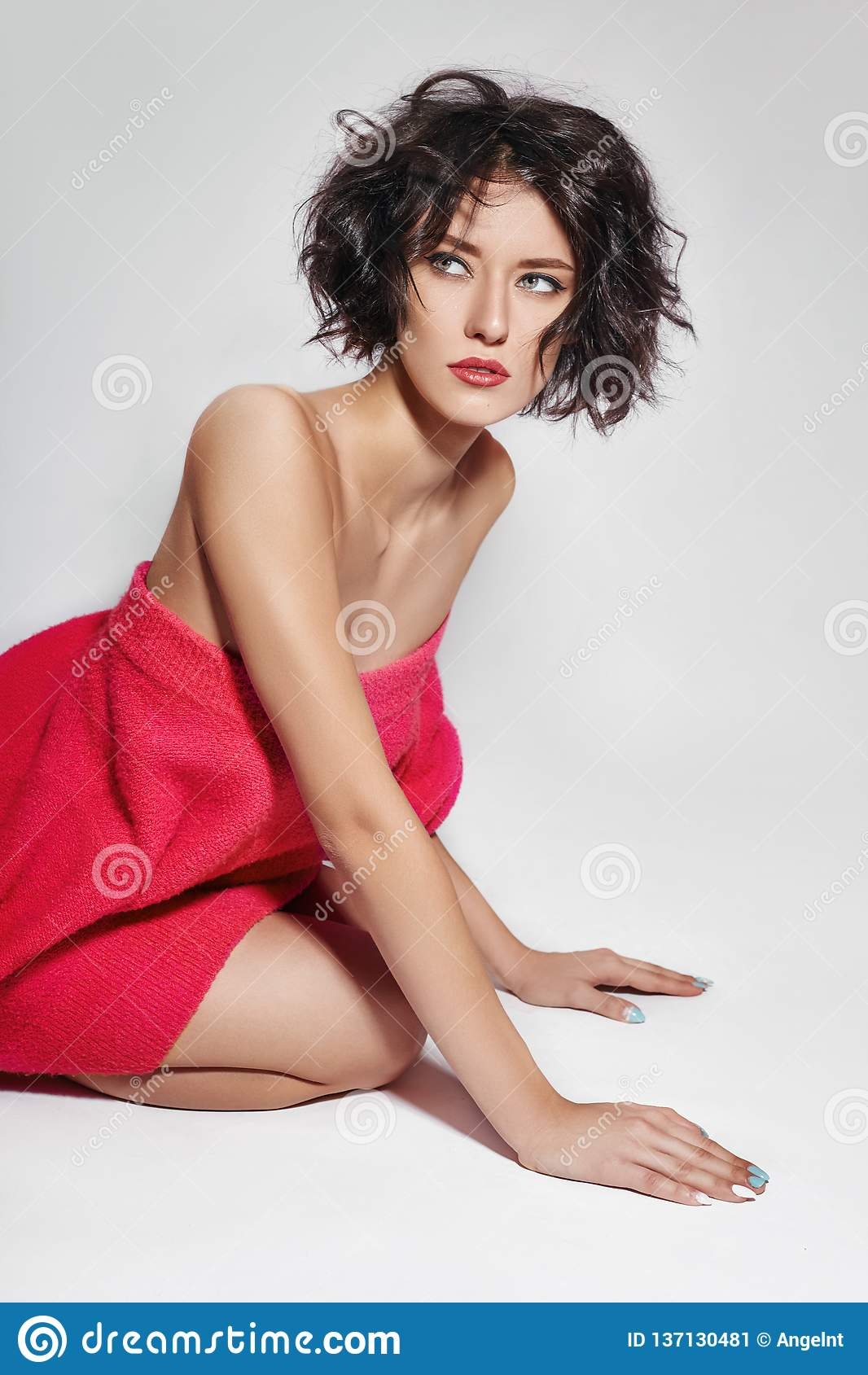 Naked woman with short hair girl posing in a red sweater on