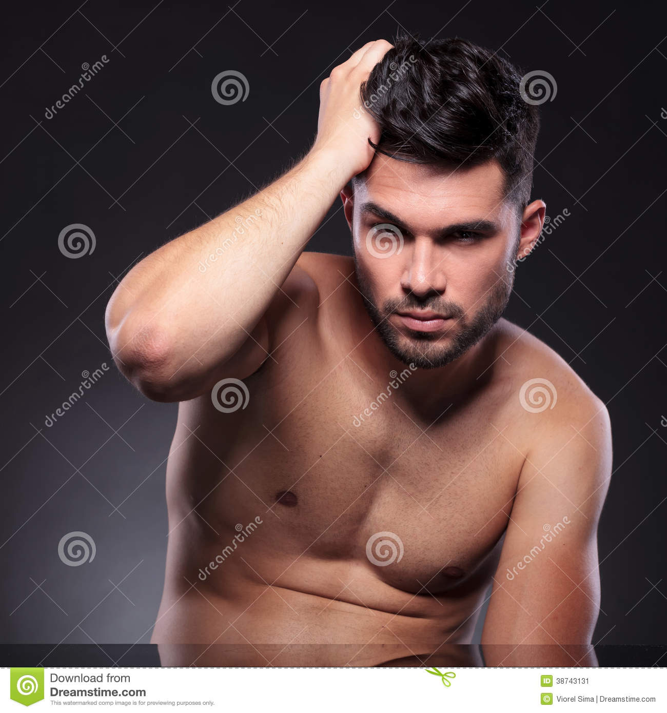 Naked young man at the desk, fixing his hair while looking into the camera.  on a black studio backgroud
