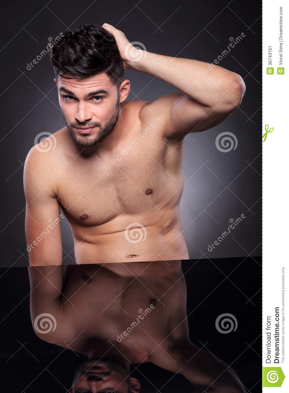 Portrait of a naked young man sitting at his desk and scratching the back  of his head while looking into the camera. on a black studio backgroud