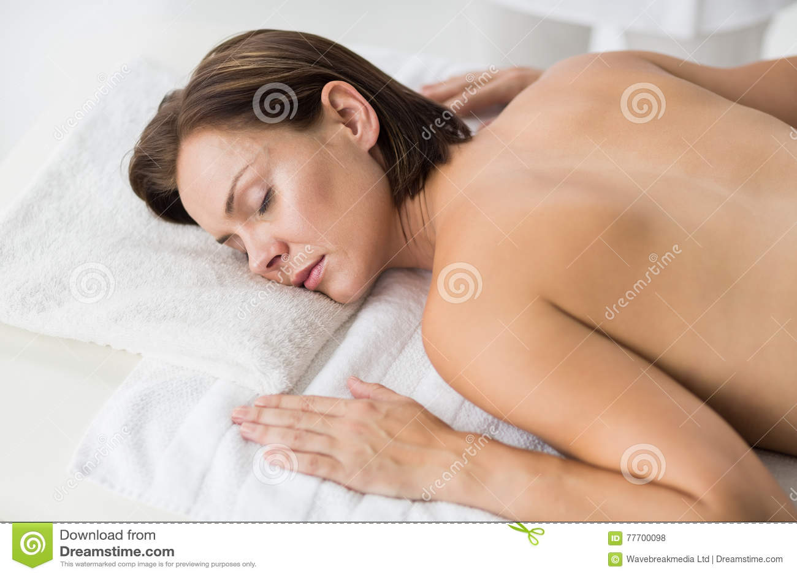 Naken kvinna som kopplar av i brunnsort