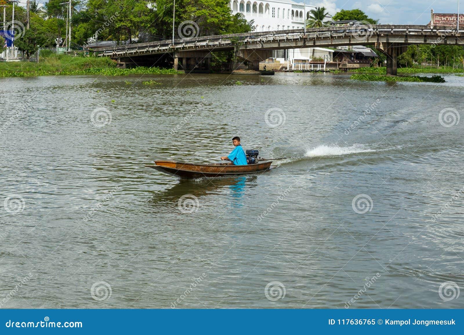 Nakhon Pathom, Tajlandia, Maj/- 26 2018: Chłopiec przejażdżka motorowa łódź, dziecko zręcznie kontroluje motorboat w rzece