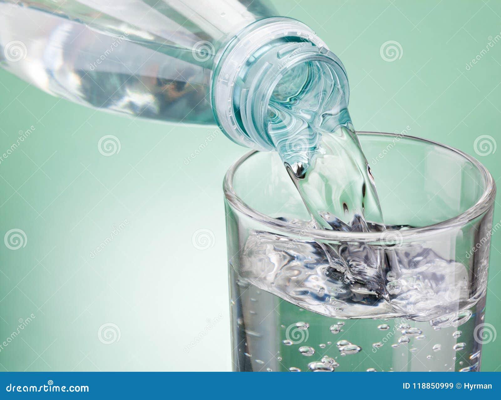 Nalewać wodę od butelki w szkło na zielonym tle