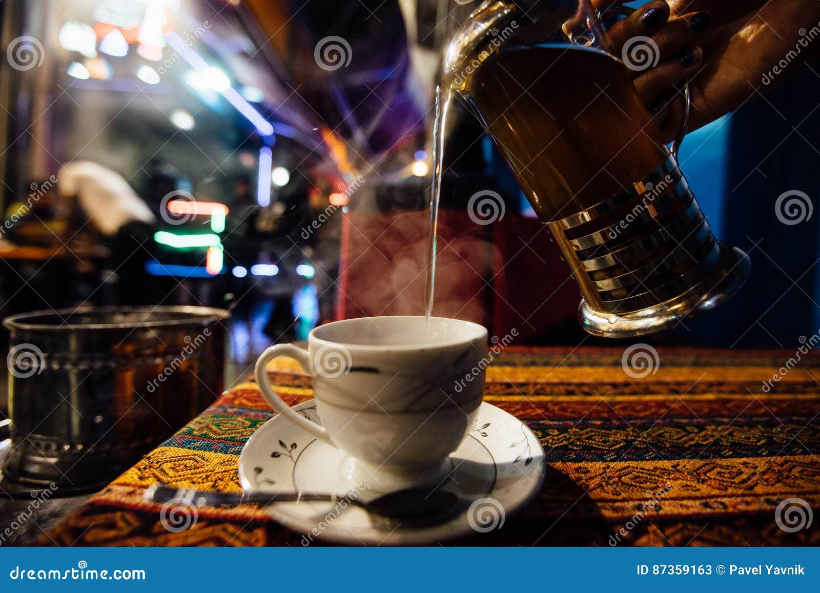 Nalewa herbaty w filiżankę przy Uliczną kawiarnią Strumienie kontrpara Arabski smak
