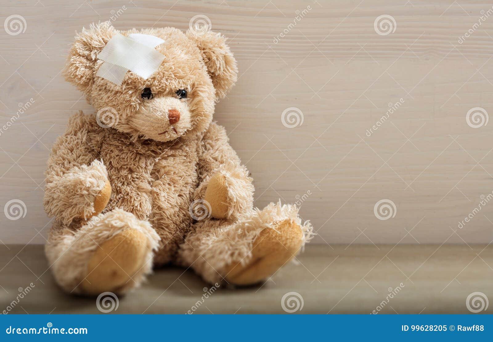 Nallebjörnen med förbinder på ett trägolv