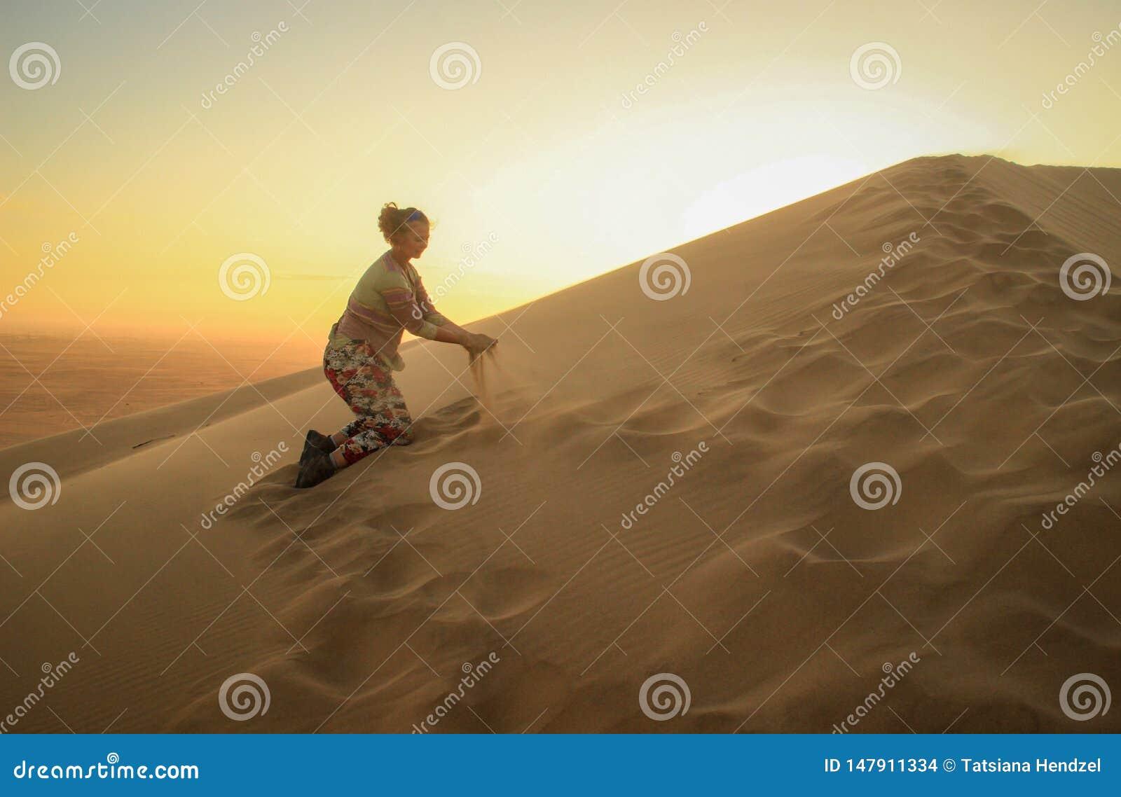 Namib öken, i den Namib-Nacluft nationalparken i Namibia Sossusvlei Turist för ung kvinna som spelar med sand