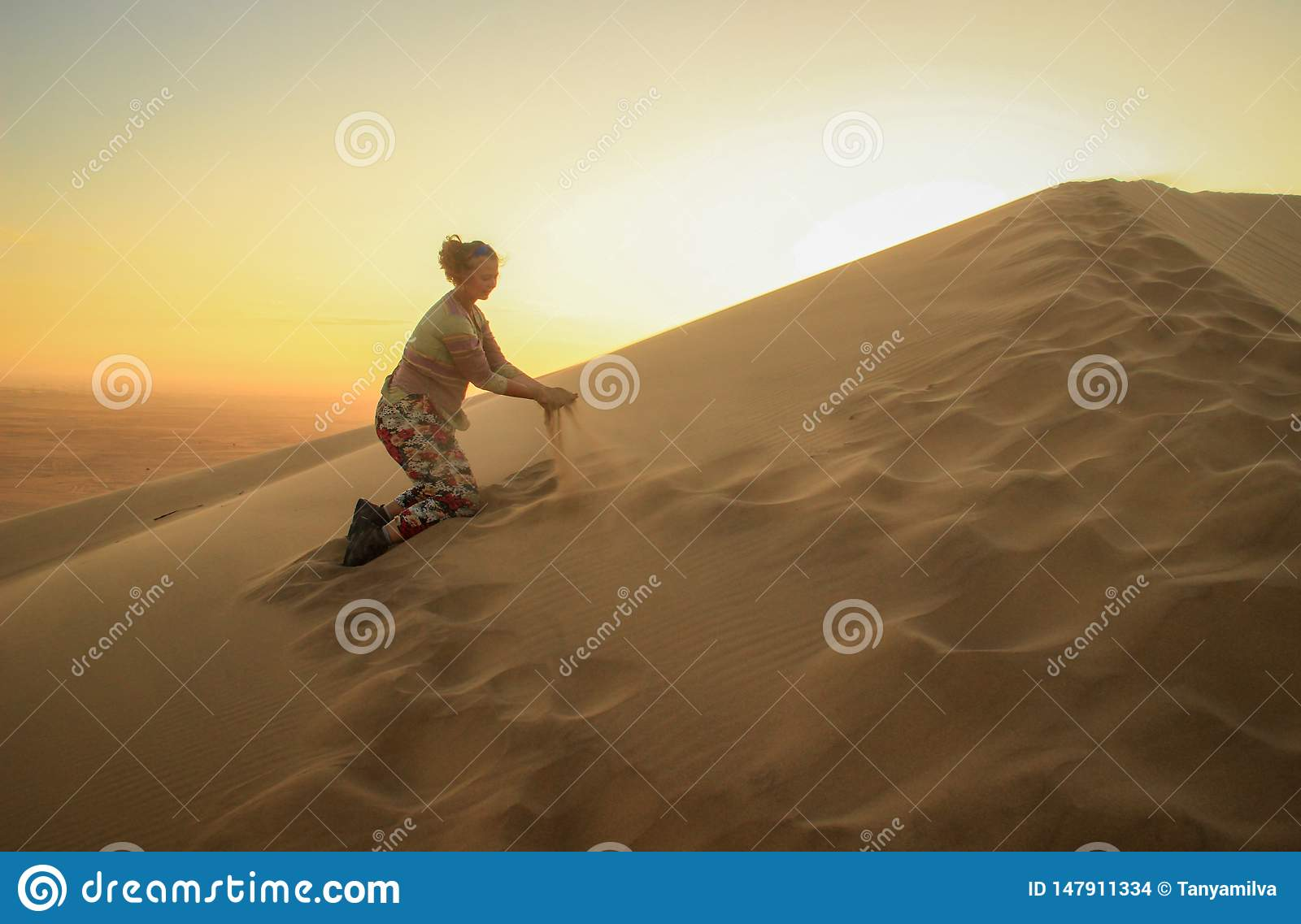 Namib Desert, in the Namib-Nacluft National Park in Namibia. Sossusvlei. Young woman tourist playing with sand
