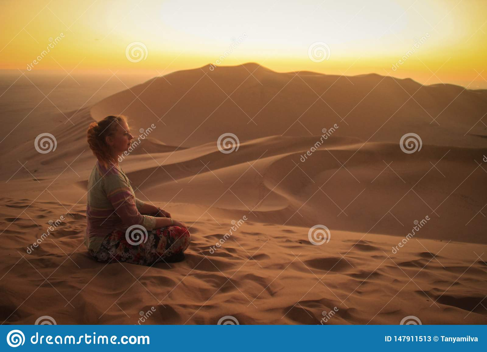 Namib ?ken, i den Namib-Nacluft nationalparken i Namibia Sossusvlei Turist för ung kvinna som gör yoga och avkoppling