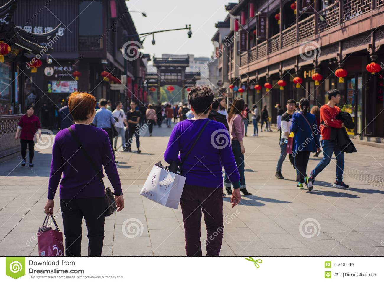 Two women in purple blouses pass by temple square.