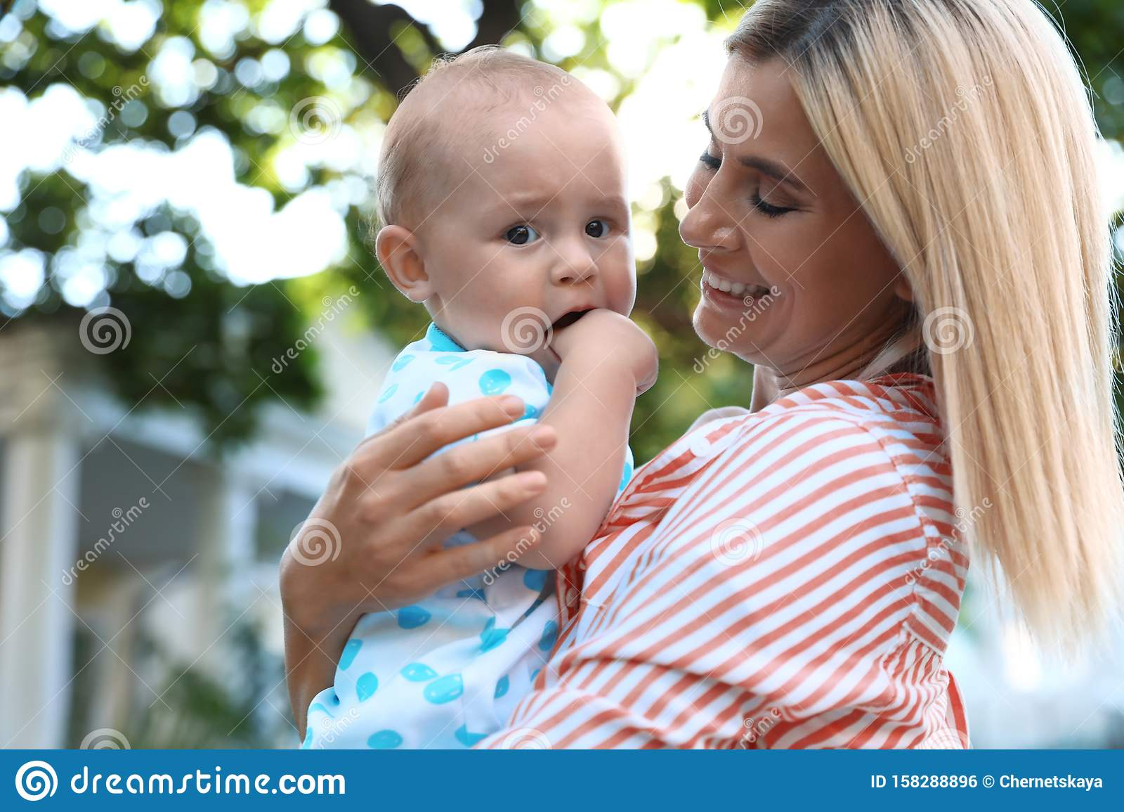 Nanny with cute baby on sunny day