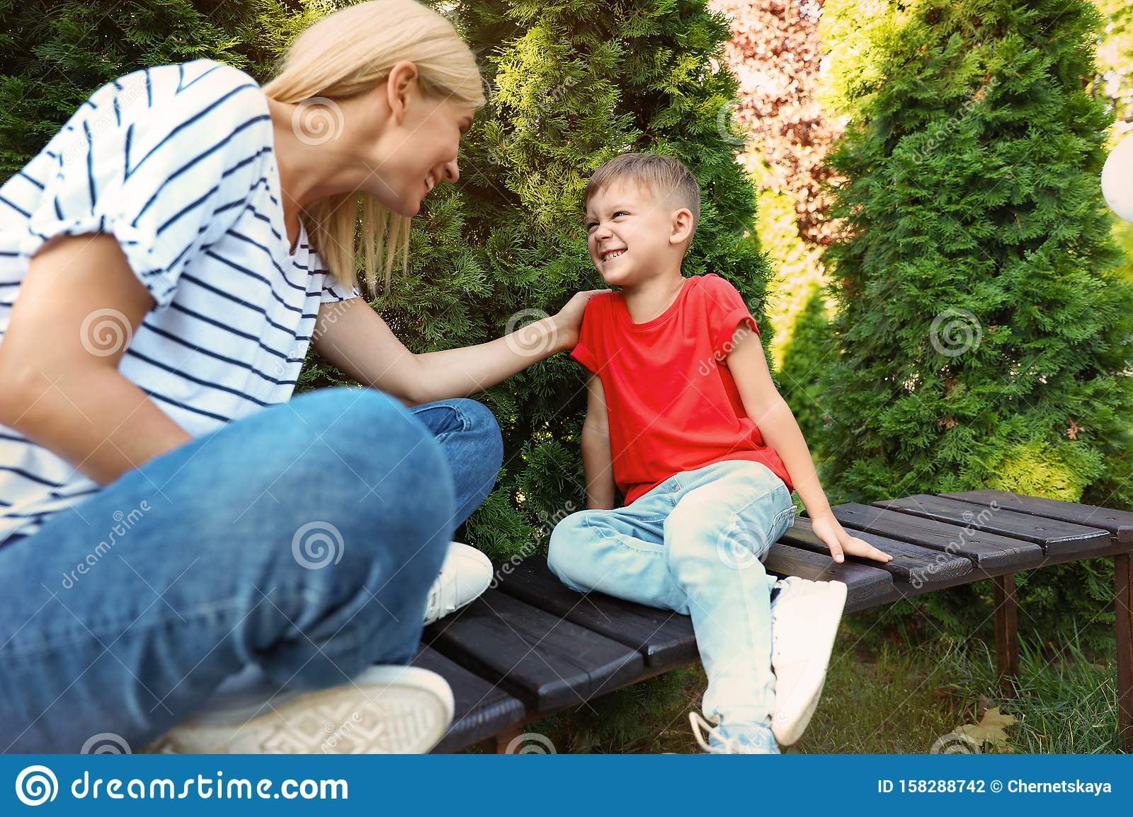 Nanny with cute little boy on bench