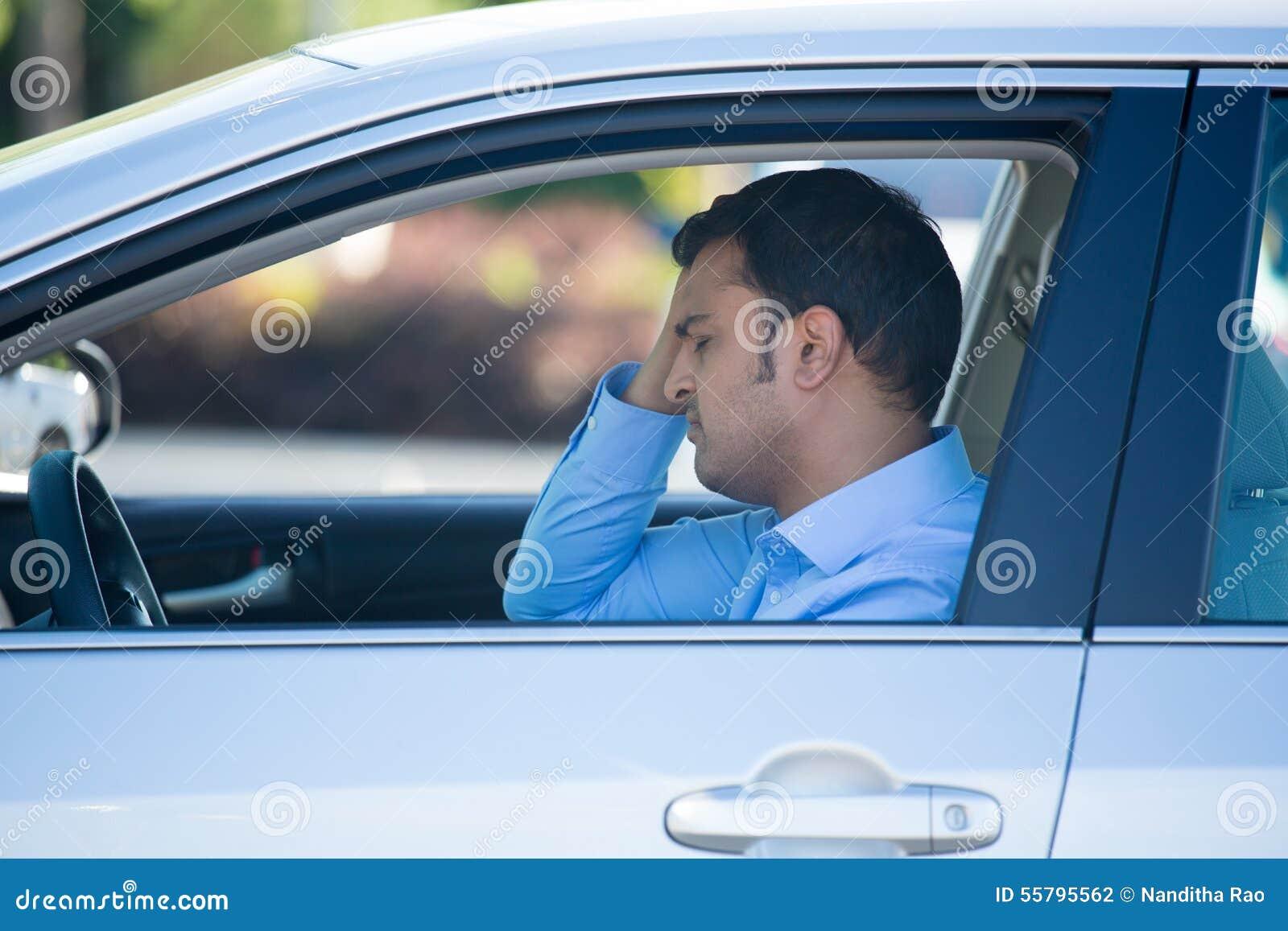 Napędowy mężczyzna spęczenie i stresujący się w samochodzie