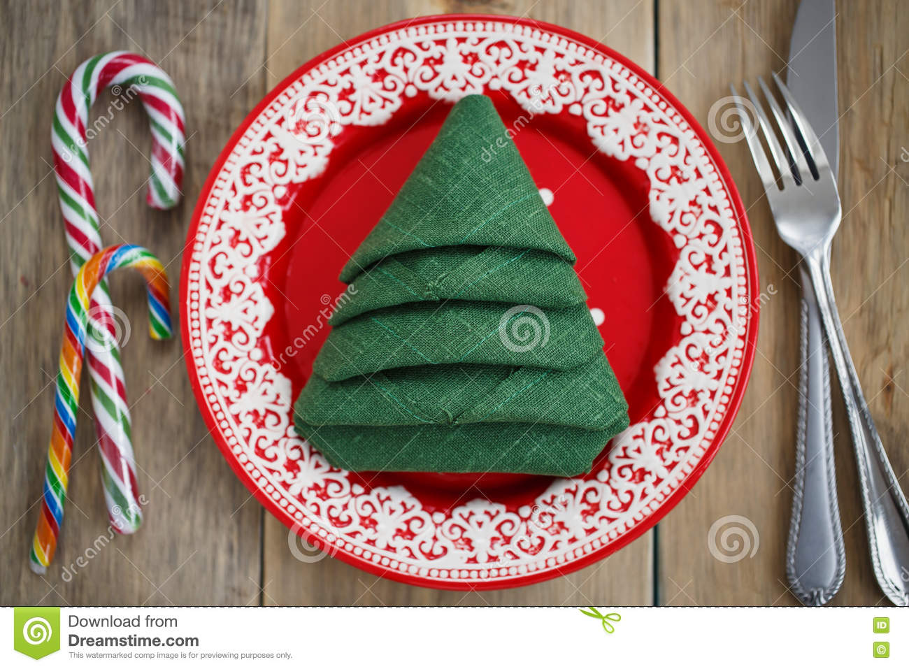 download napkin folded in the shape of a christmas tree in a red plate stock image