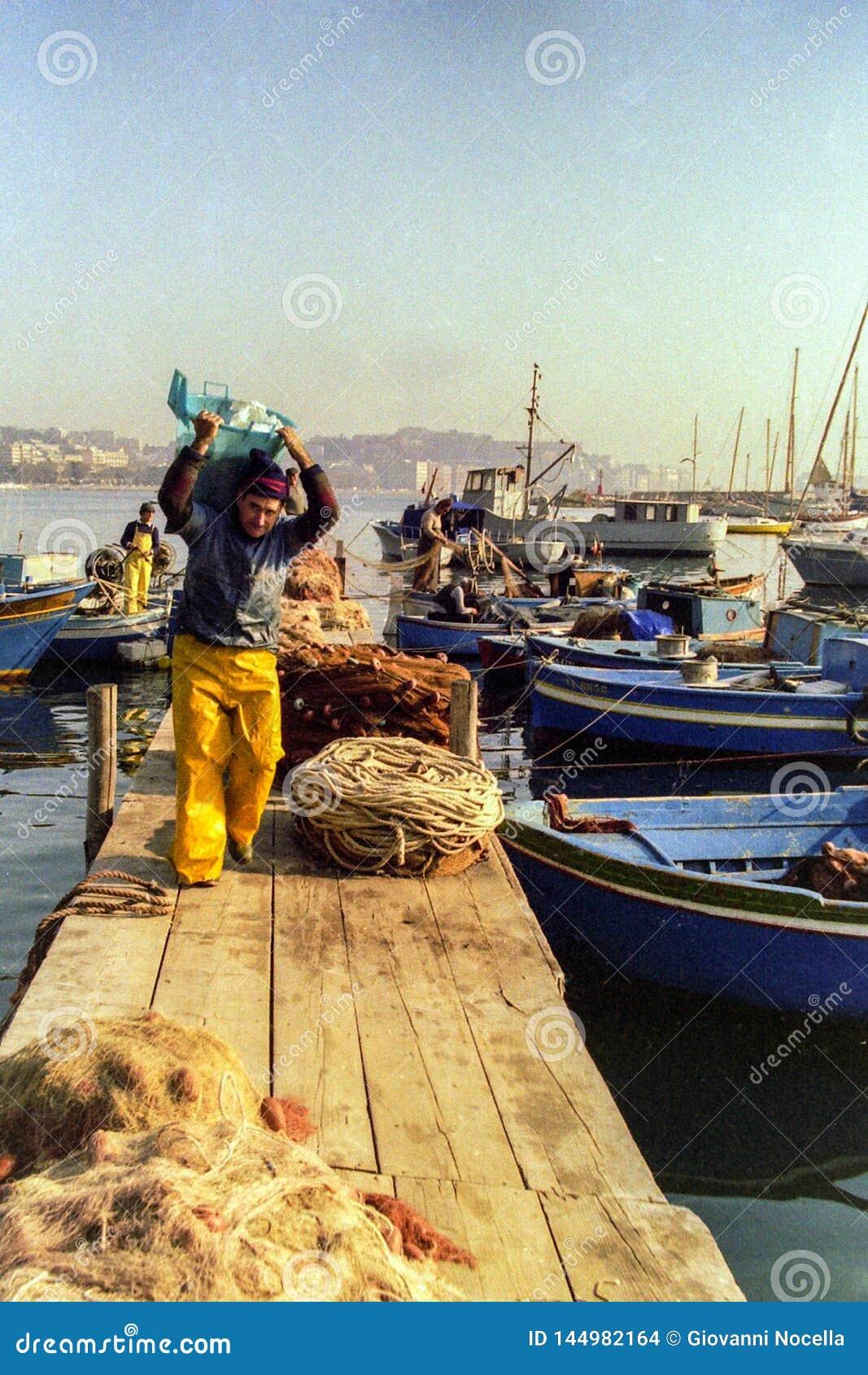 NAPLES ITALIEN, 1988 - fiskare förtöjer deras fartyg i porten av Mergellina och förlägger deras förtjänar på slutet av en