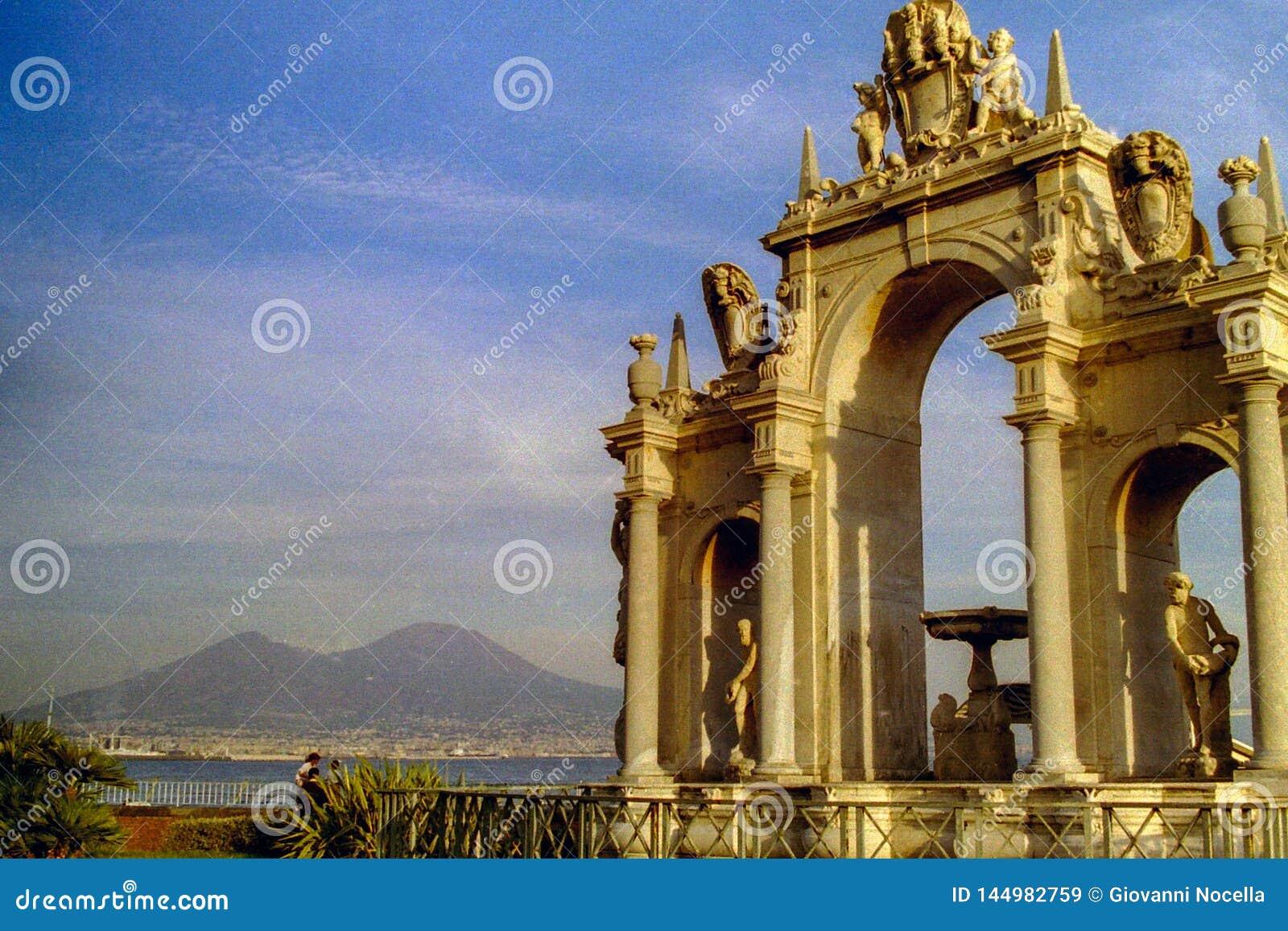 NAPLES, WŁOCHY, 1995 - Vesuvius jest tłem monumentalny Fontana Del Gigante lokalizować na Naples nabrzeżu