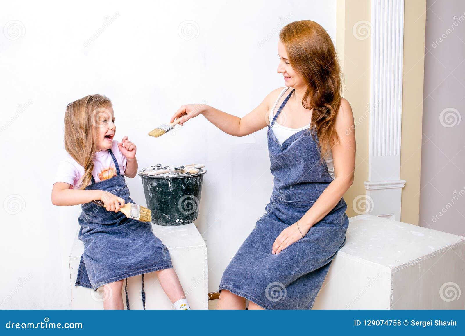 Naprawa w mieszkaniu Szczęśliwa rodziny matka, córka w fartuchach i przygotowywaliśmy malować ścianę z białą farbą Siedzi z muśni