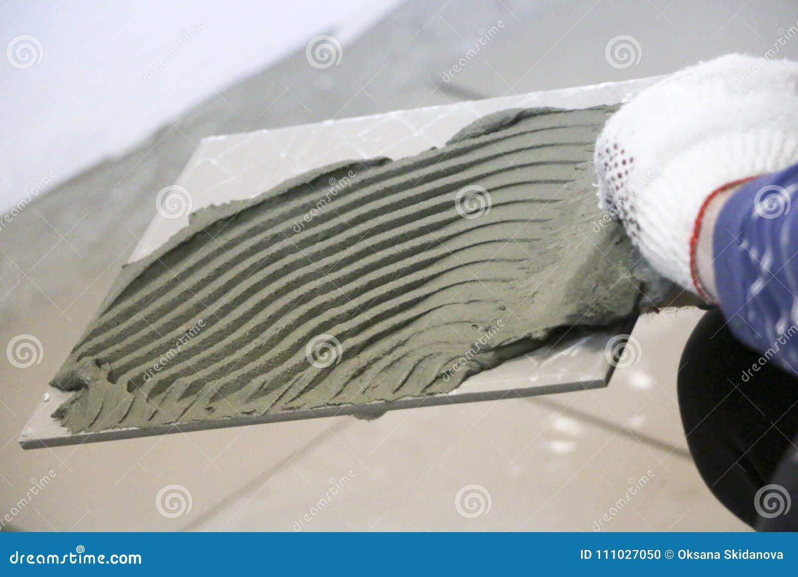 Naprawa - wewnętrzna dekoracja Kłaść podłogowe ceramiczne płytki Mężczyzna ` s ręk kaflarz w rękawiczkach z szpachelki rozszerzan