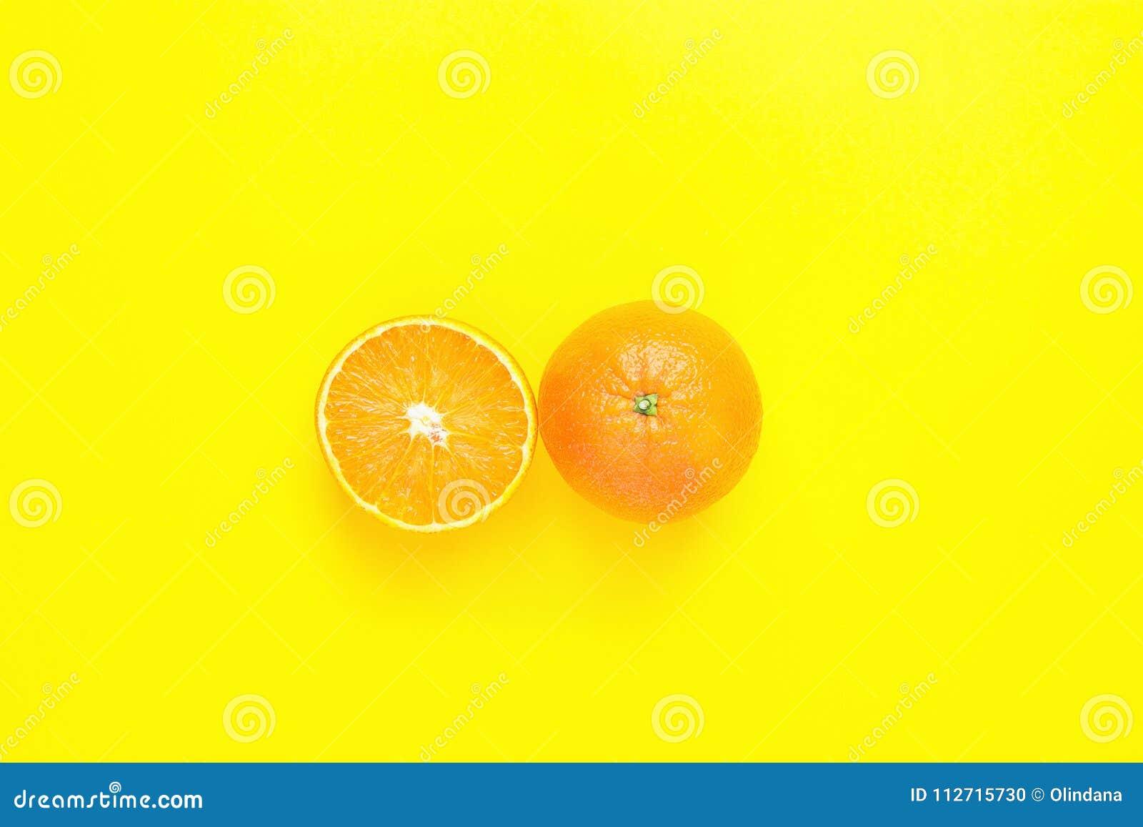 Naranja entera y partida en dos jugosa madura en fondo amarillo sólido Frutas tropicales del vegano del Detox del verano de la di
