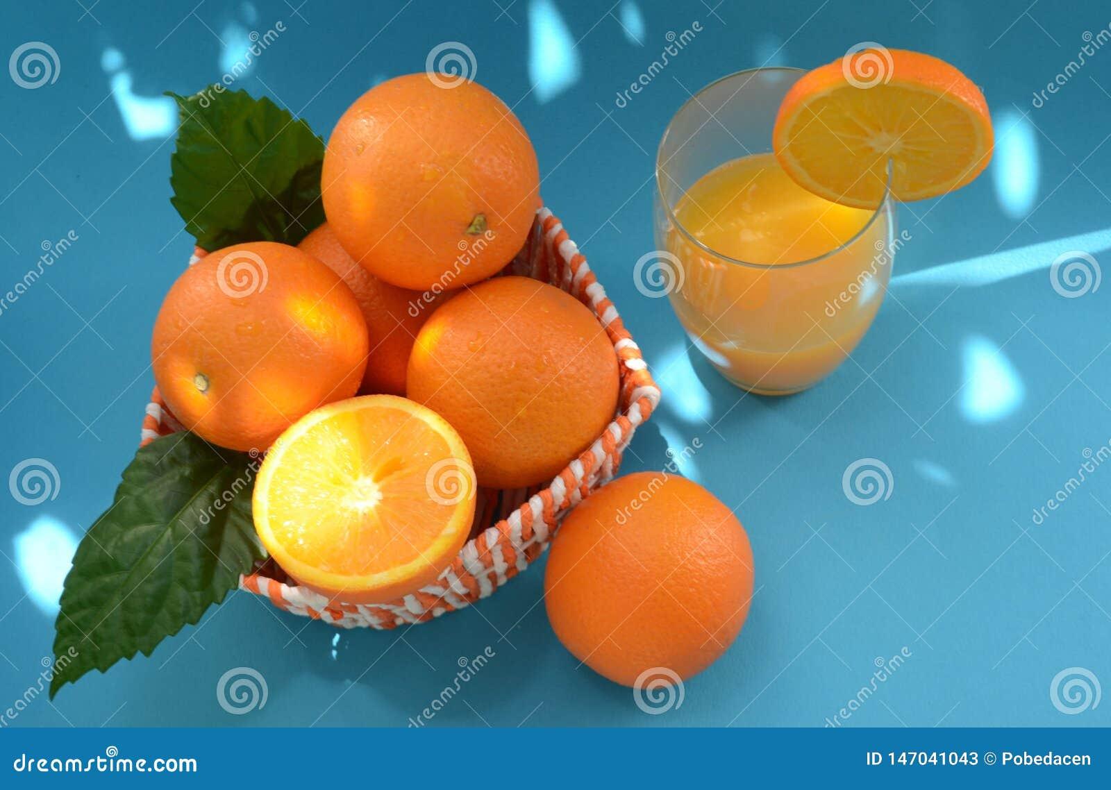 Naranjas y zumo de naranja recientemente exprimido en un fondo azul con puntos culminantes brillantes del sol