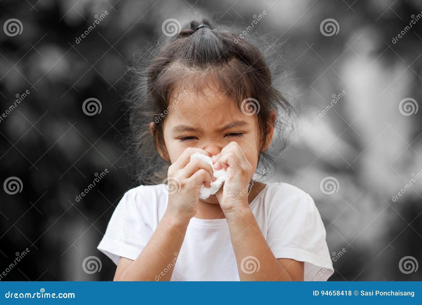 Nariz de limpeza ou de limpeza da menina asiática pequena doente com tecido