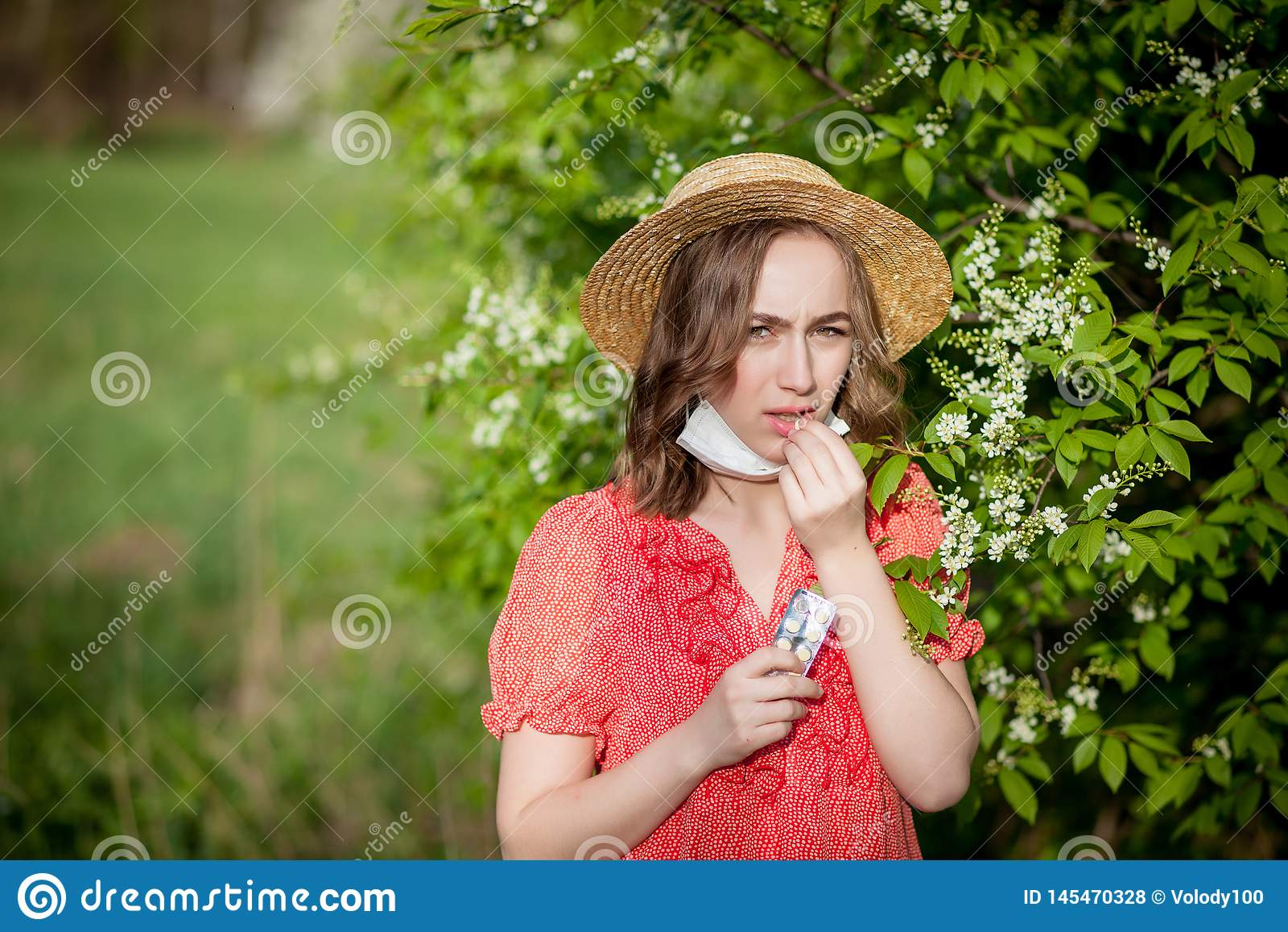 Nariz que sopla de la chica joven y estornudo en tejido delante del ?rbol floreciente Alerg?nicos estacionales que afectan a gent