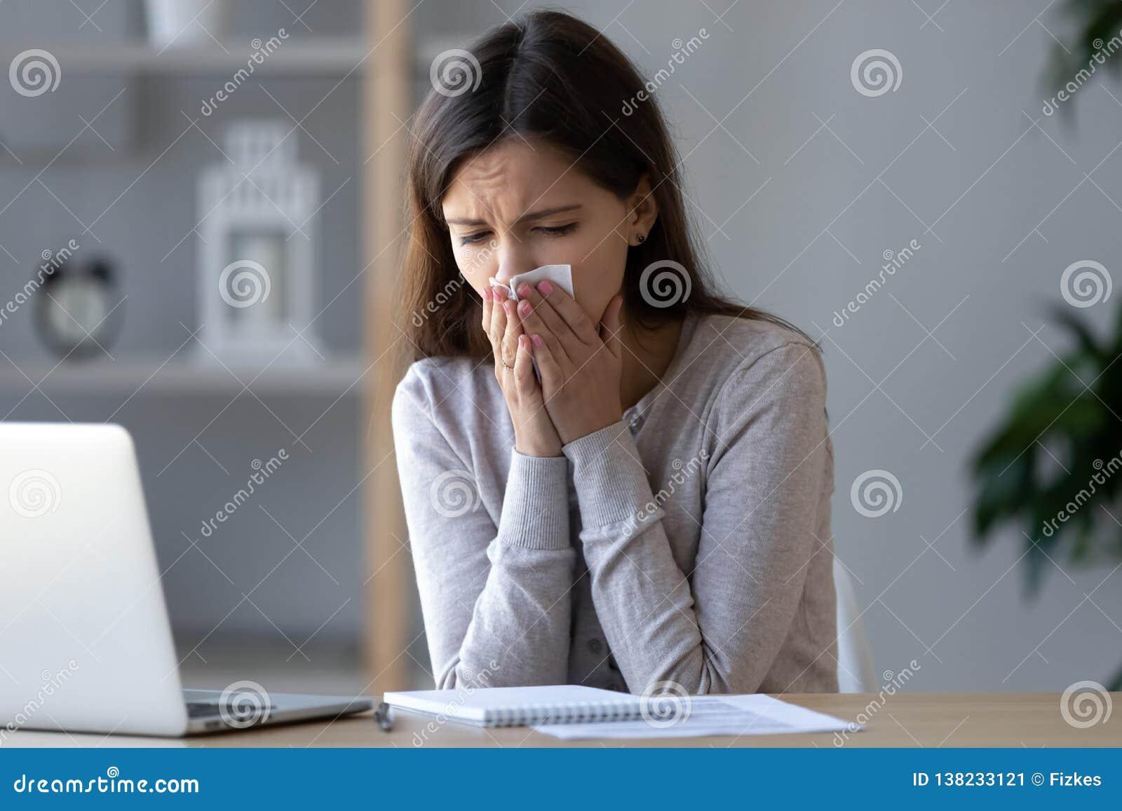 Nariz que sopla del trabajador enfermo alérgico que estornuda en tejido en el lugar de trabajo