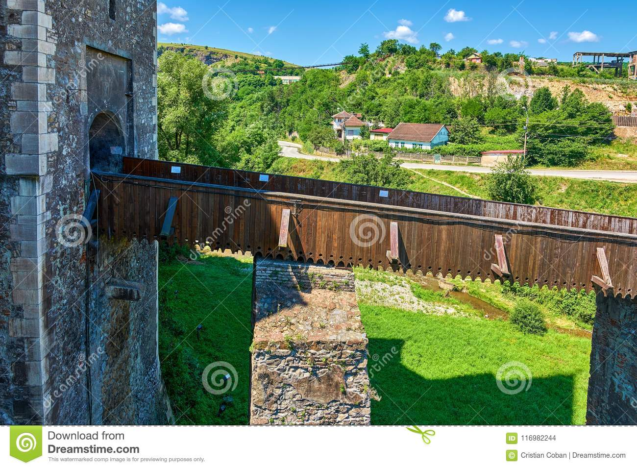 Narrow Foot Bridge Over Moat Of A Medieval Castle Fort With Stone Walls