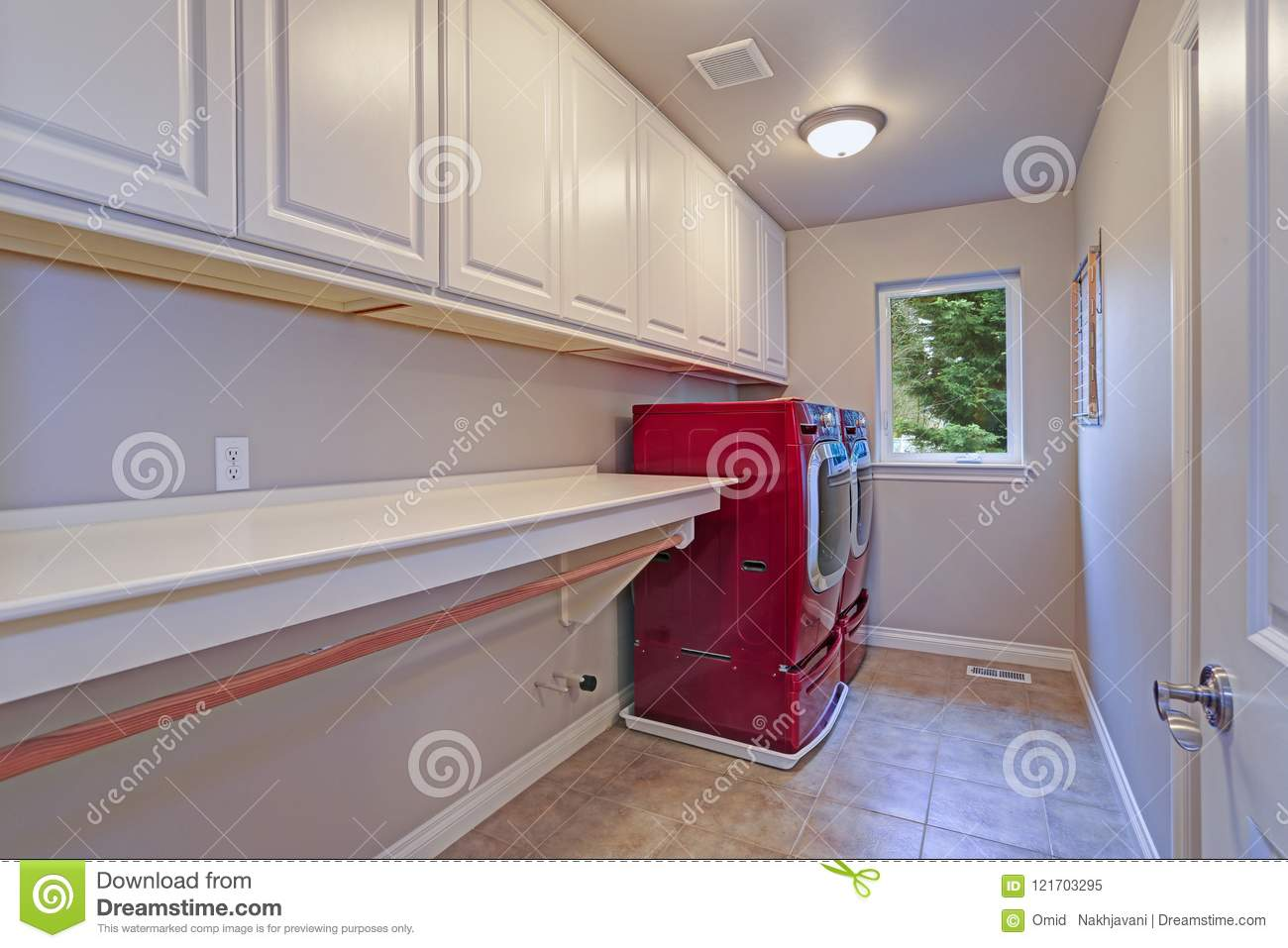 narrow home laundry with white cabinets and red appliances stock rh dreamstime com White Custom Cabinets White Laundry Room Doors