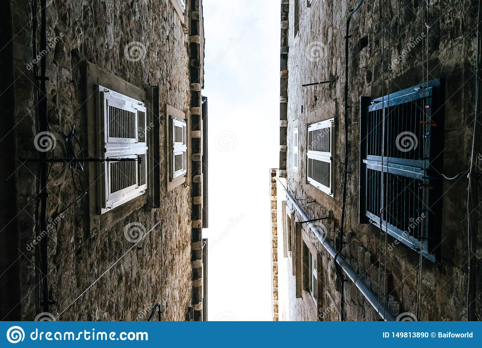 The narrow streets of the old city of Dubrovnik in Croatia, the bottom view of the sky between the stone walls of houses
