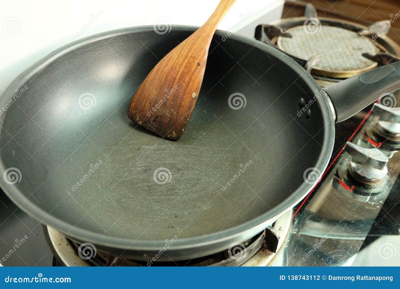 Narysy na teflon smaży nieckę z szpachelką na benzynowej kuchence