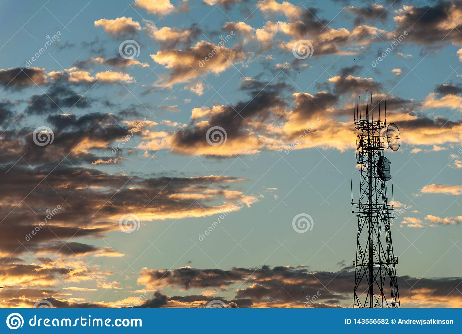 Nascer do sol atrás de uma torre de comunicações para o rádio e a transmissão de tevê