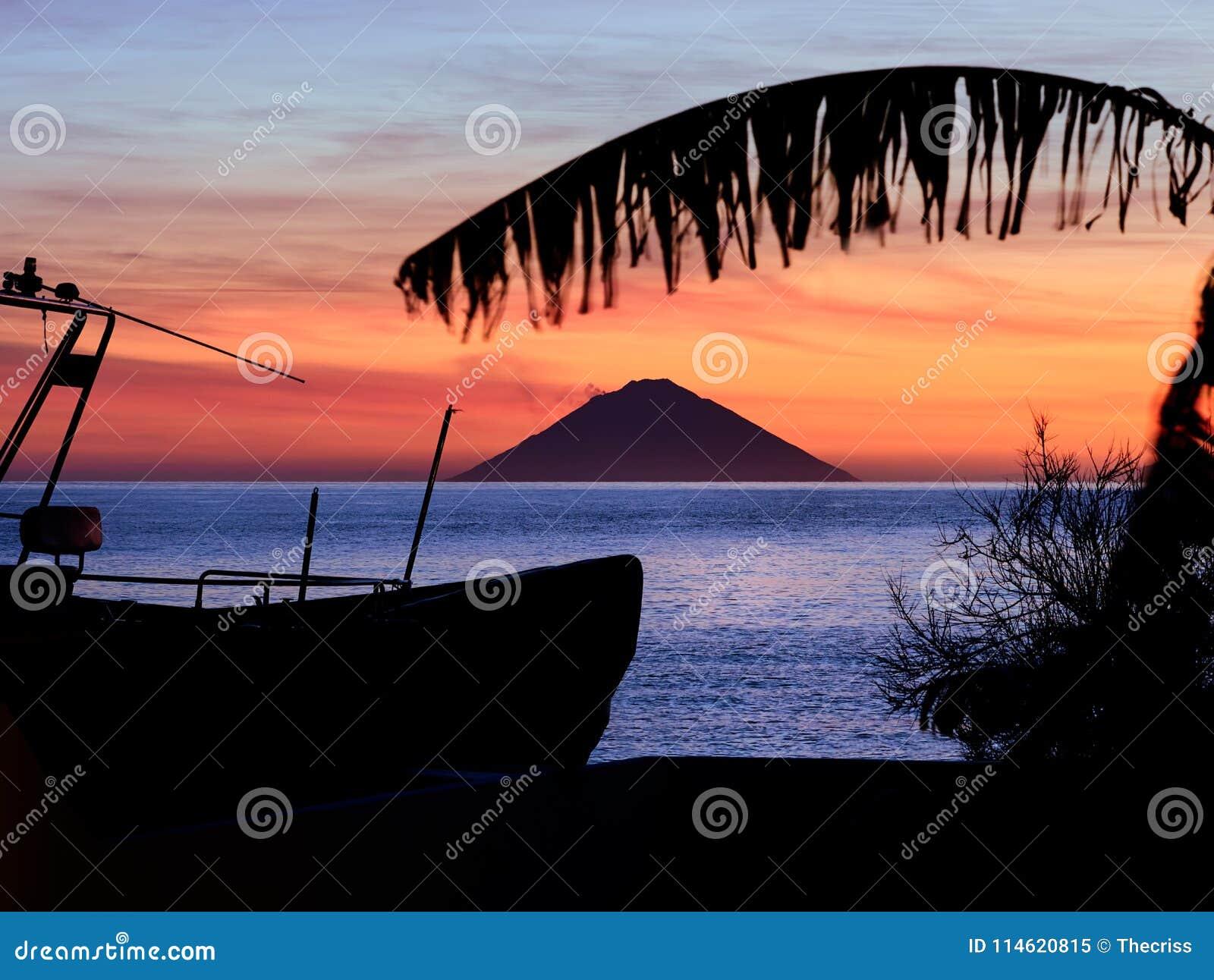 Nascer do sol bonito com o vulcão de Stromboli visto da ilha do Salina nas ilhas eólias, Sicília, Itália
