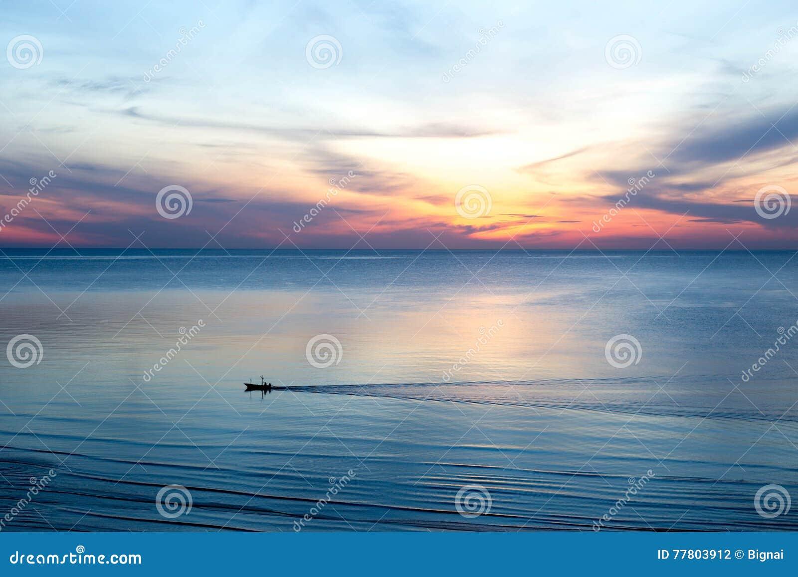 Nascer do sol bonito com os barcos de pesca tailandeses no mar