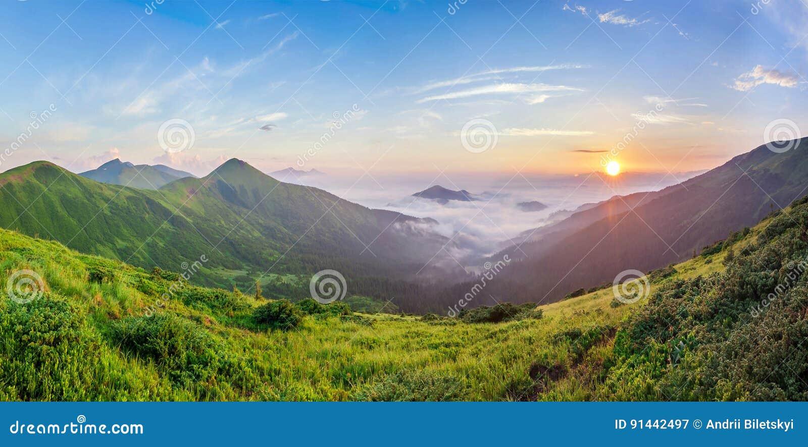 Nascer do sol bonito nas montanhas com névoa branca abaixo do panorama