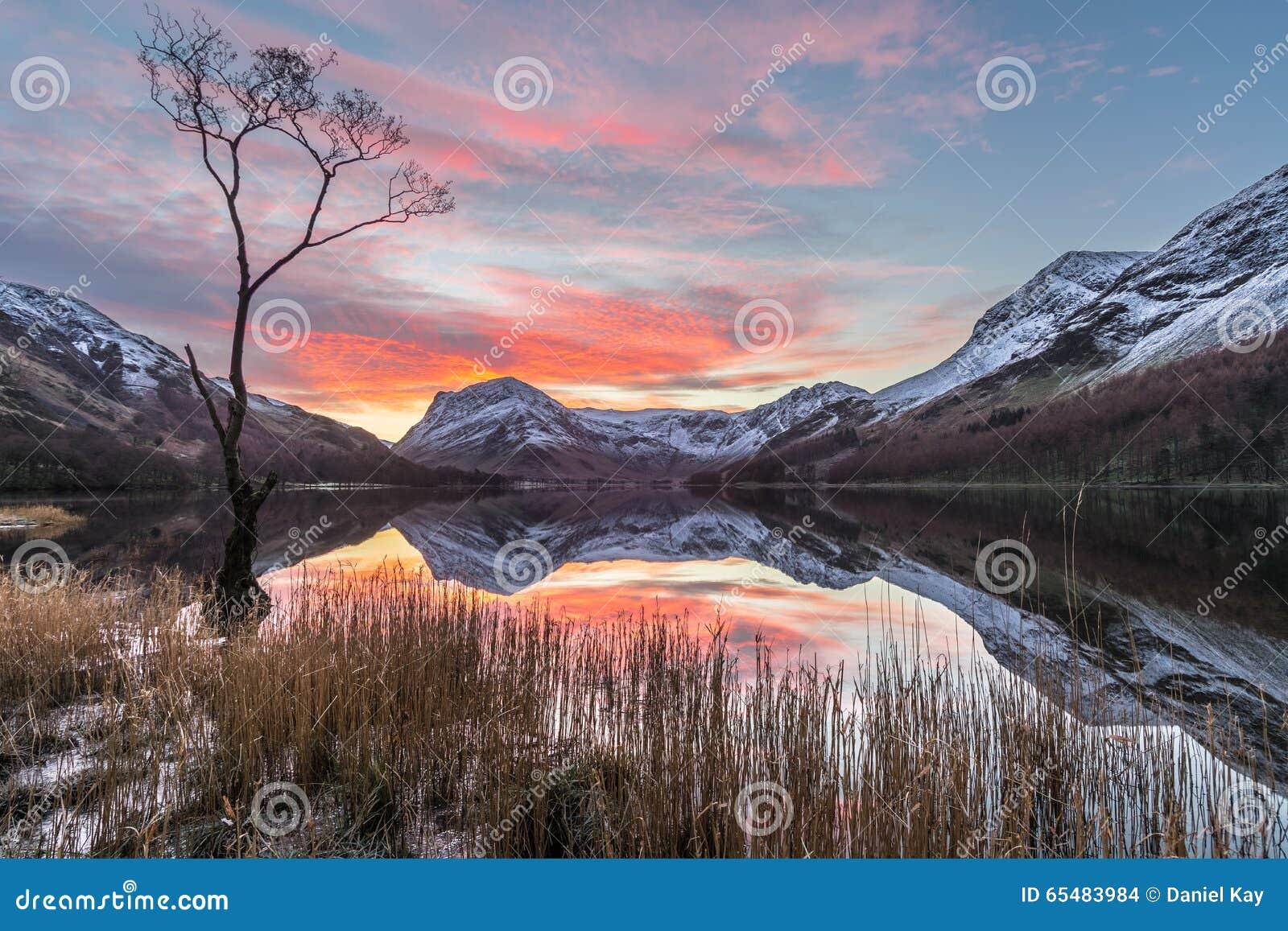 Nascer do sol cor-de-rosa e alaranjado vibrante bonito do inverno em Buttermere no distrito do lago, Reino Unido