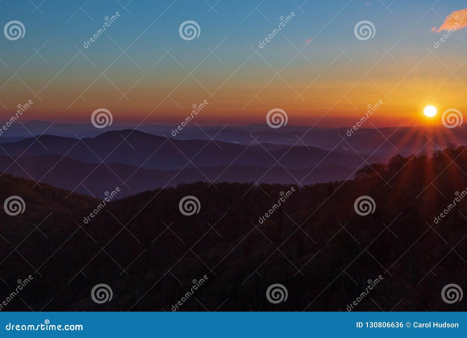 Nascer do sol em Ridge Parkway azul no outono com céu azul e sugestão de uma nuvem