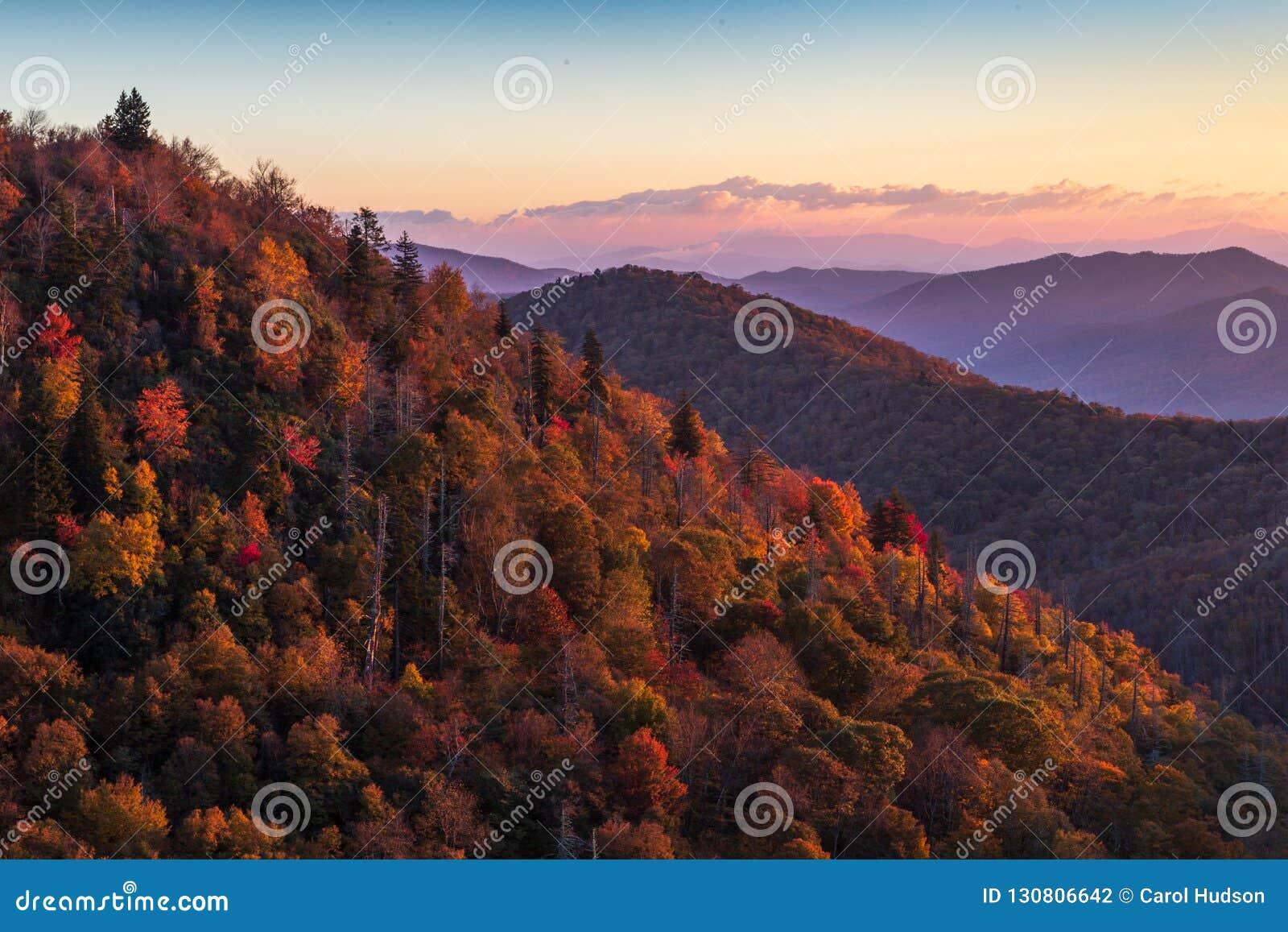 Nascer do sol em Ridge Parkway azul no outono que ilumina árvores coloridas no montanhês