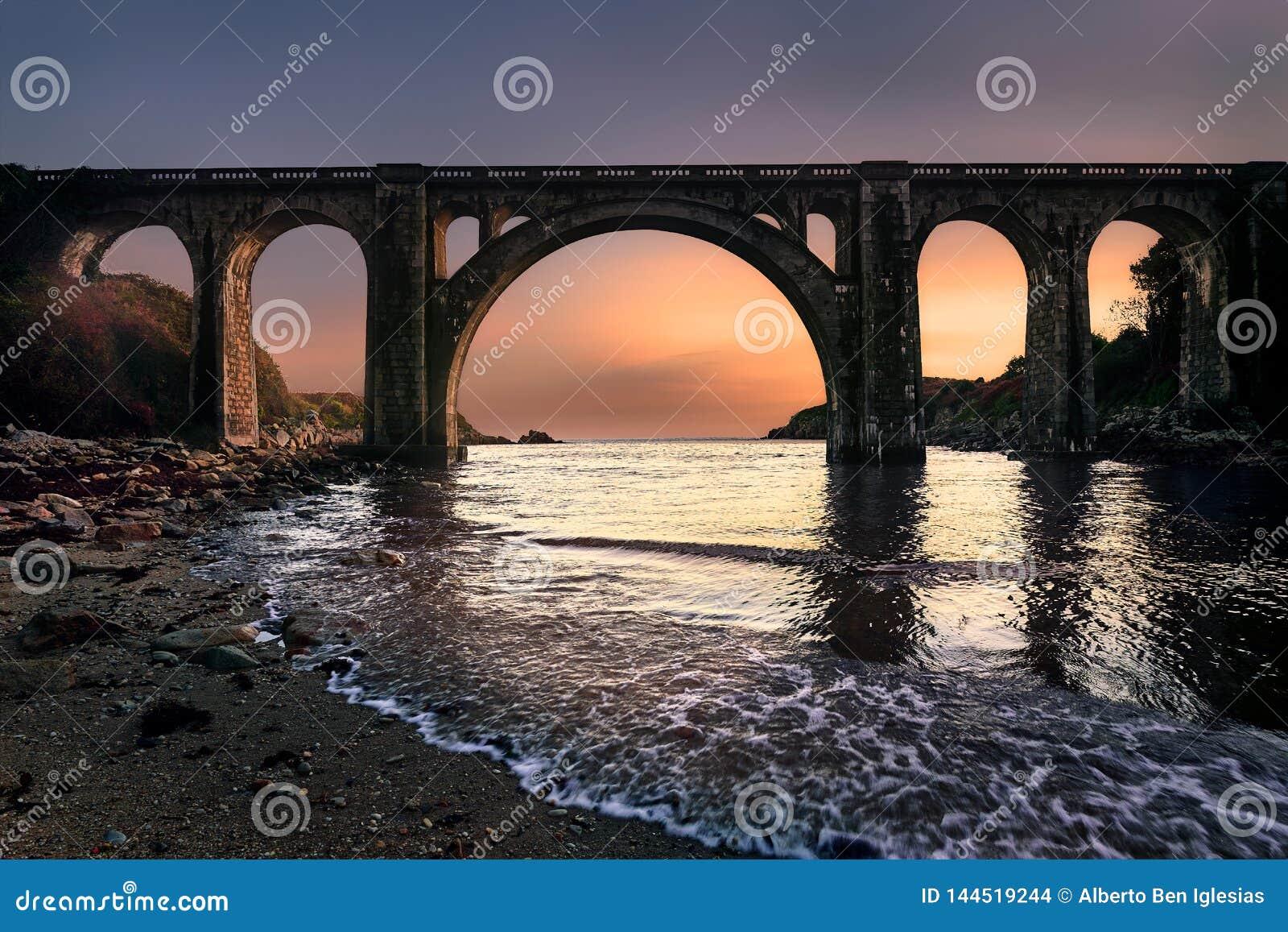 Nascer do sol em uma ponte sobre a praia da