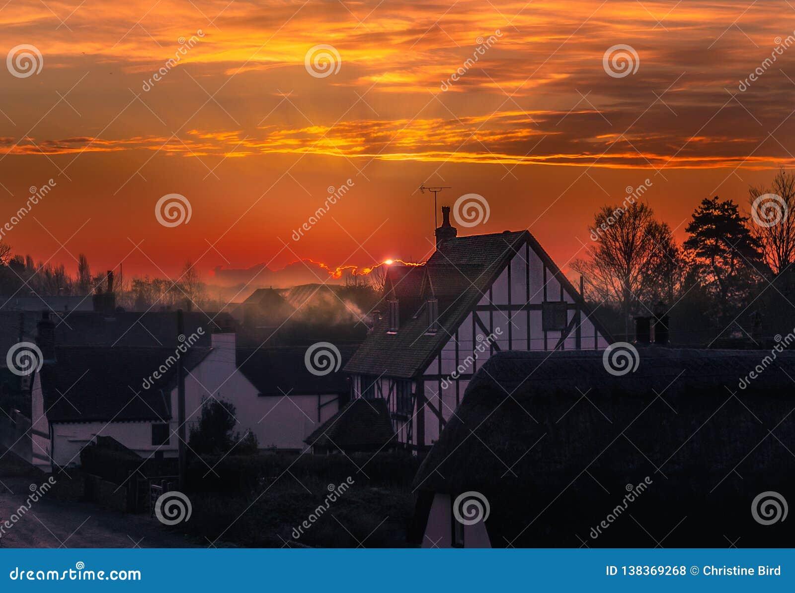 Nascer do sol na vila de Monkton, Kent, Reino Unido O sol apenas está aparecendo atrás de uma nuvem produzindo uma luz da borda e