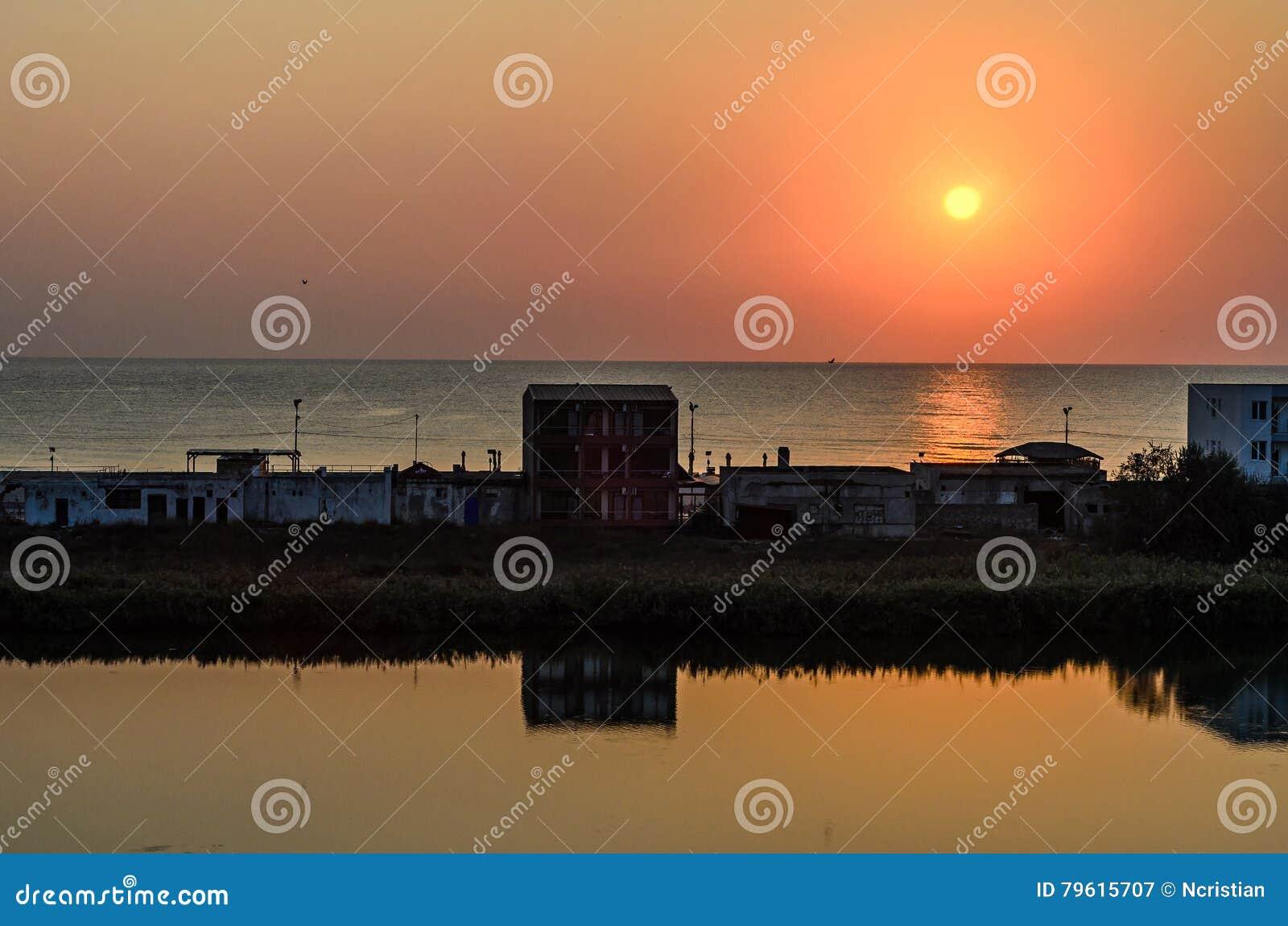 Nascer do sol no beira-mar, na areia e na água clara, a costa do Mar Negro