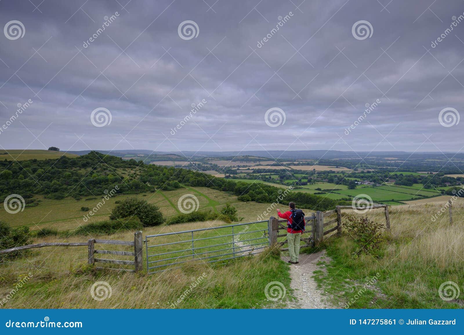 Nascer do sol nublado nebuloso do ver?o sobre o passeio sul da maneira das penas de um caminhante masculino envelhecido meio com
