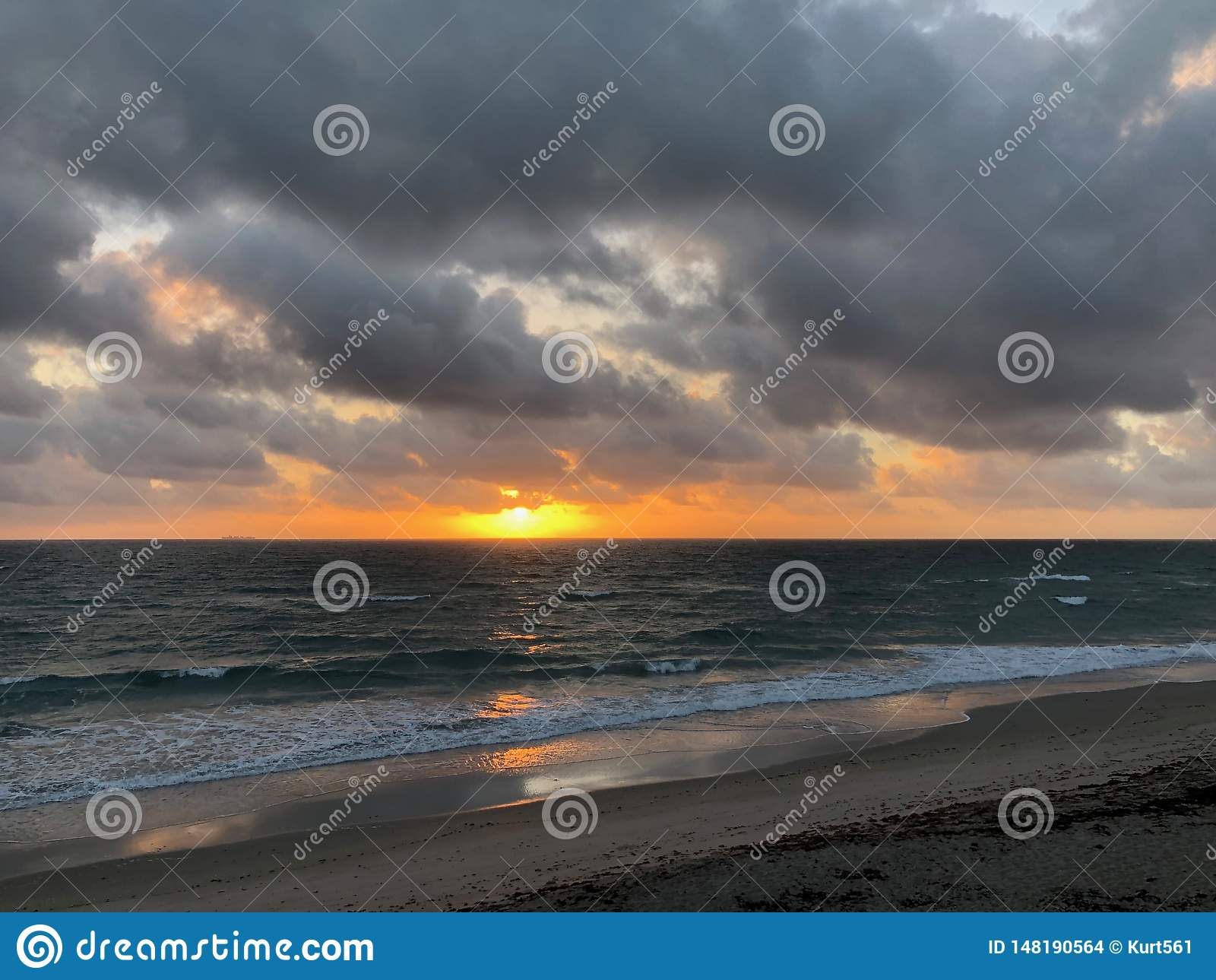 Nascer do sol sobre o oceano com nuvens escuras