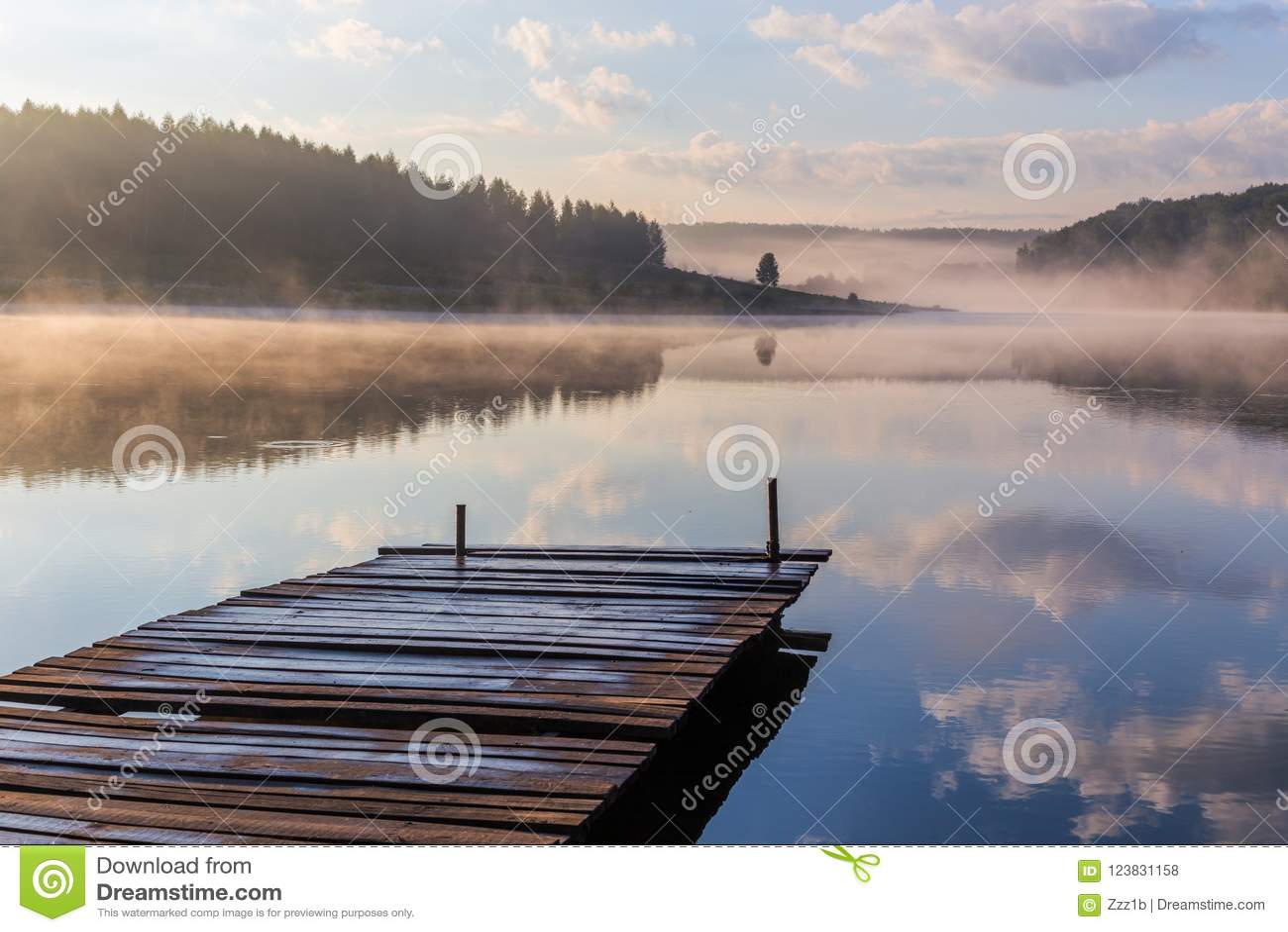 Nascer do sol sobre o rio nevoento com um cais de madeira