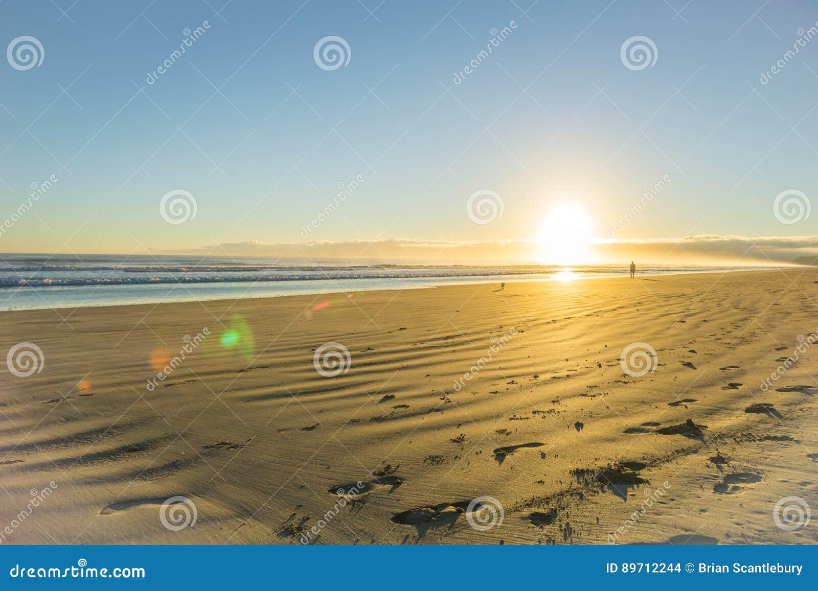 Nascer do sol sobre o Sandy Beach liso largo em Ohope Whakatane