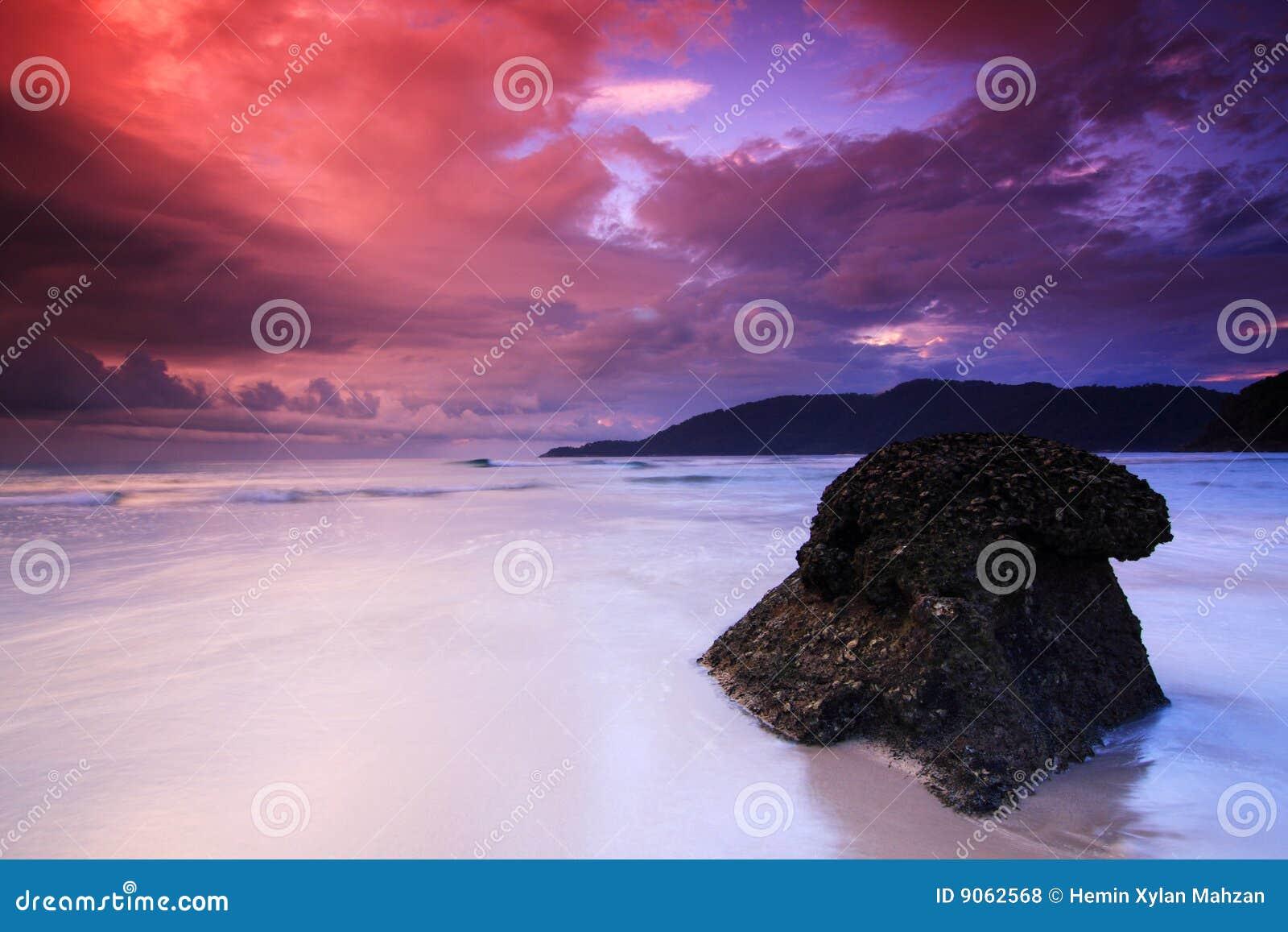 Nascer do sol vermelho do céu na praia do console de Perhentian