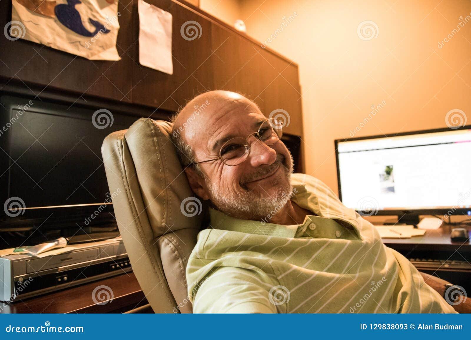 Nascido no Baby Boom calvo idoso de sorriso do homem que reclina na cadeira executiva de couro na mesa com seu monitor do computa