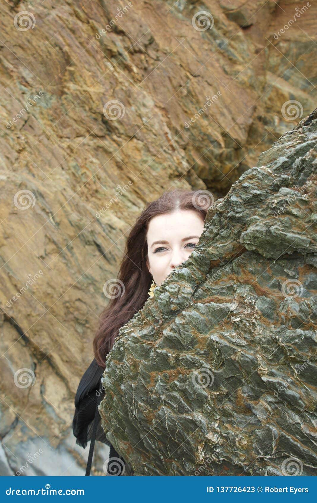 Nascondino: la ragazza castana dai capelli lunghi si nasconde dietro una roccia su una spiaggia