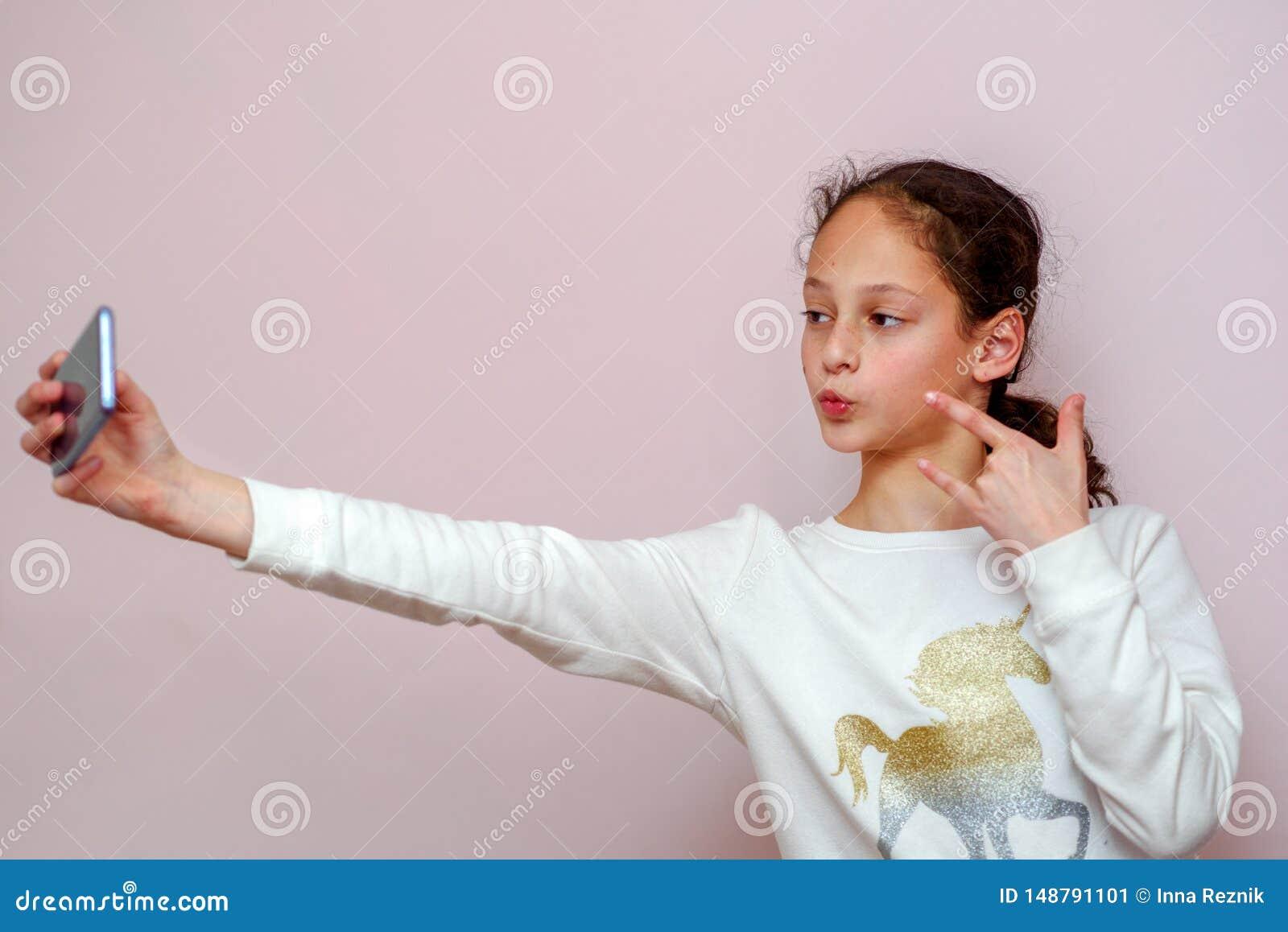 Nastolatek dziewczyna bierze selfie z jej telefonem kom?rkowym na r??owym tle
